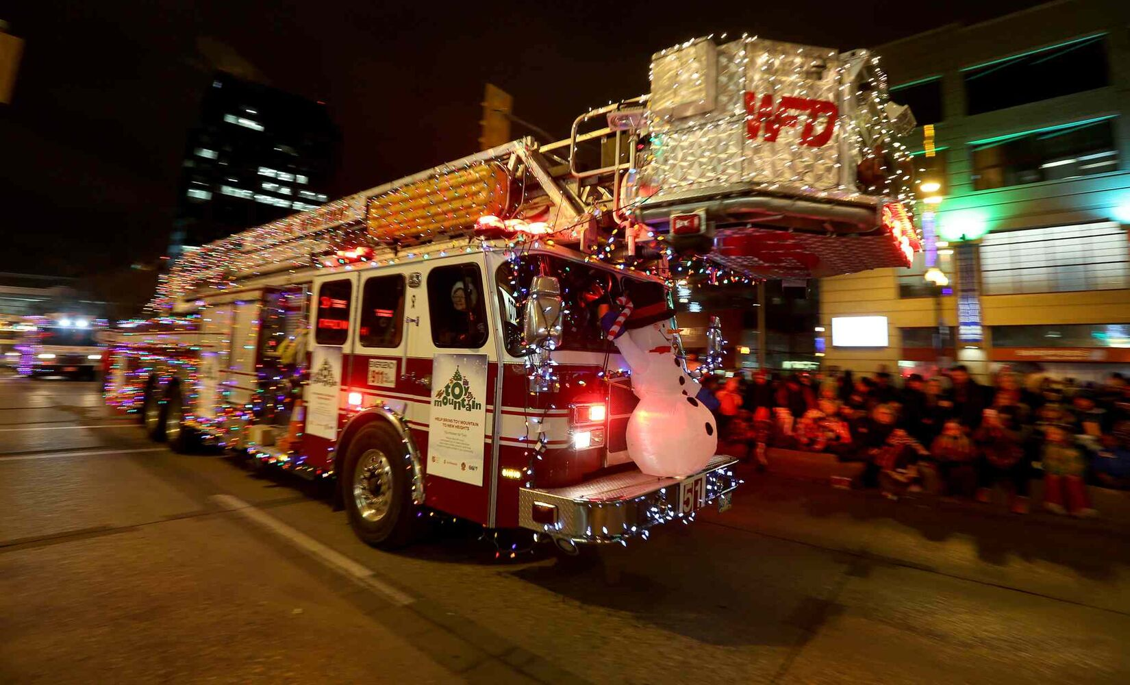 A fire truck decked out in lights and decorations makes its way down Portage Avenue. (TREVOR HAGAN / WINNIPEG FREE PRESS)