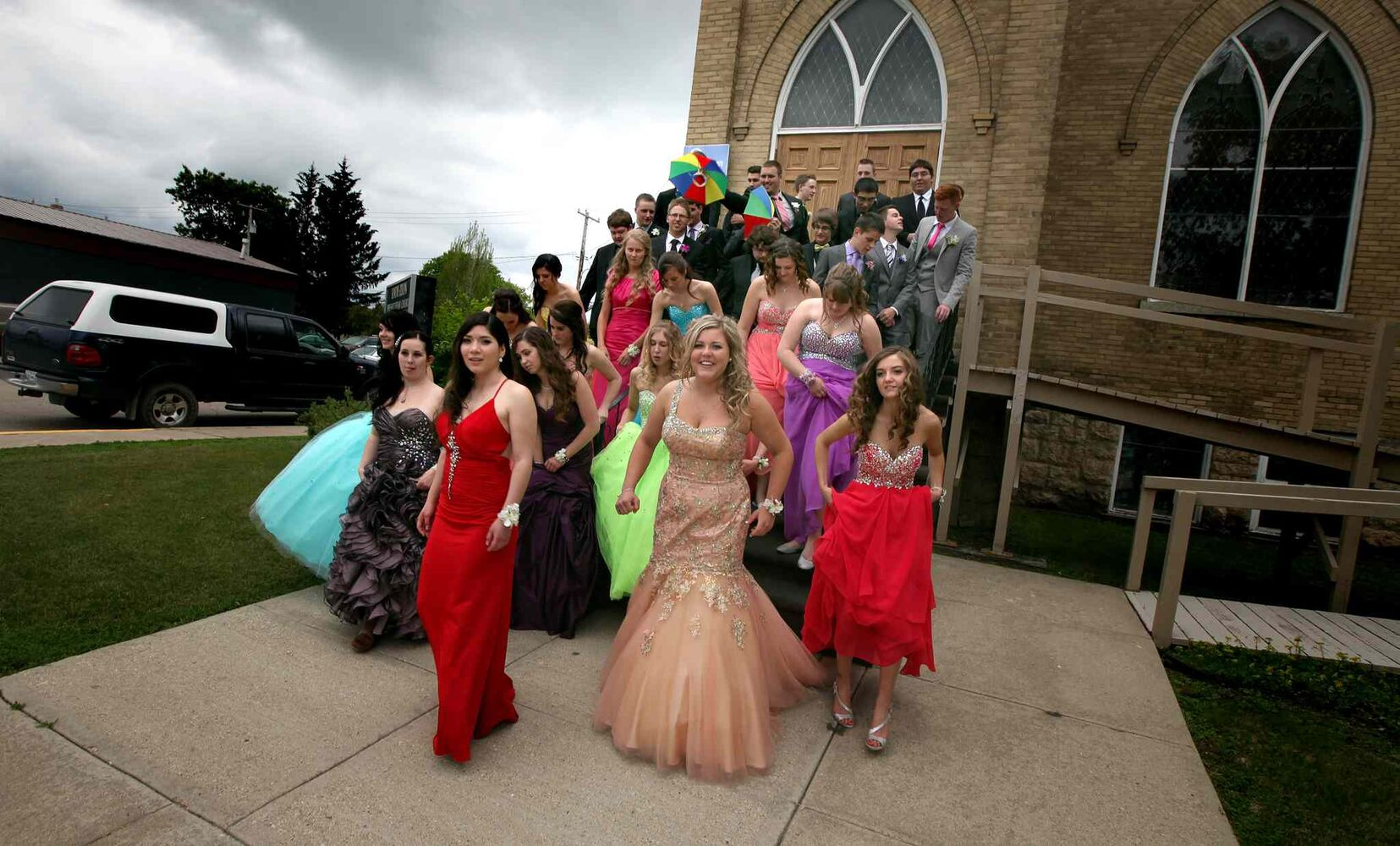 Carberry's class of 14 walks down the church steps used as risers for their graduation photo Wednesday. (Phil Hossack / Winnipeg Free Press)