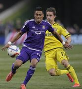 Orlando City's Darwin Ceren, left, tries to clear the ball as Columbus Crew's Ethan Finlay defends during the first half of an MLS soccer game Saturday, April 18, 2015, in Columbus, Ohio. (AP Photo/Jay LaPrete)