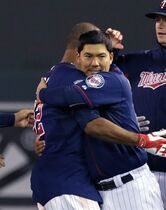 Minnesota Twins' Kurt Suzuki, right, hugs Aaron Hicks after Hicks' walk-off single in the ninth inning of a baseball game against the Detroit Tigers, Tuesday, Sept. 16, 2014, in Minneapolis. Suzuki's double in the ninth tied the score. The Twins won 4-3. (AP Photo/Jim Mone)