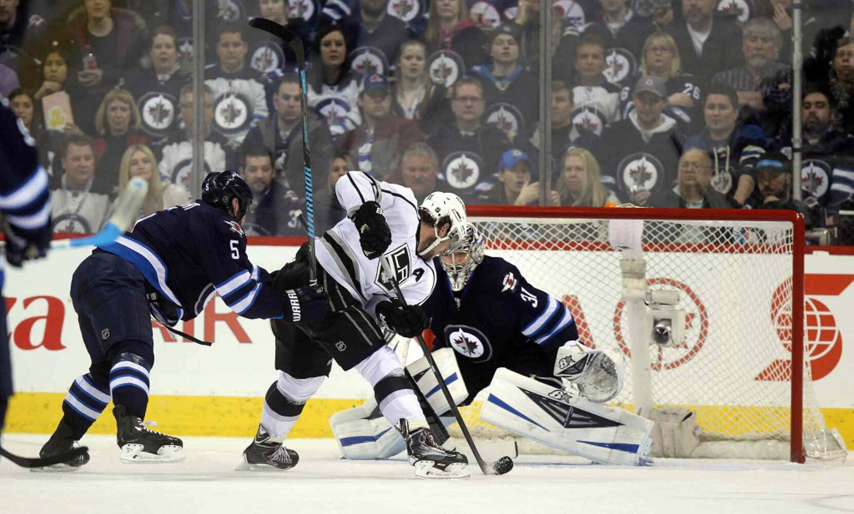 An L.A. King moves in on Ondrej Pavelec behind Jets defenceman Mark Stuart in second period action.