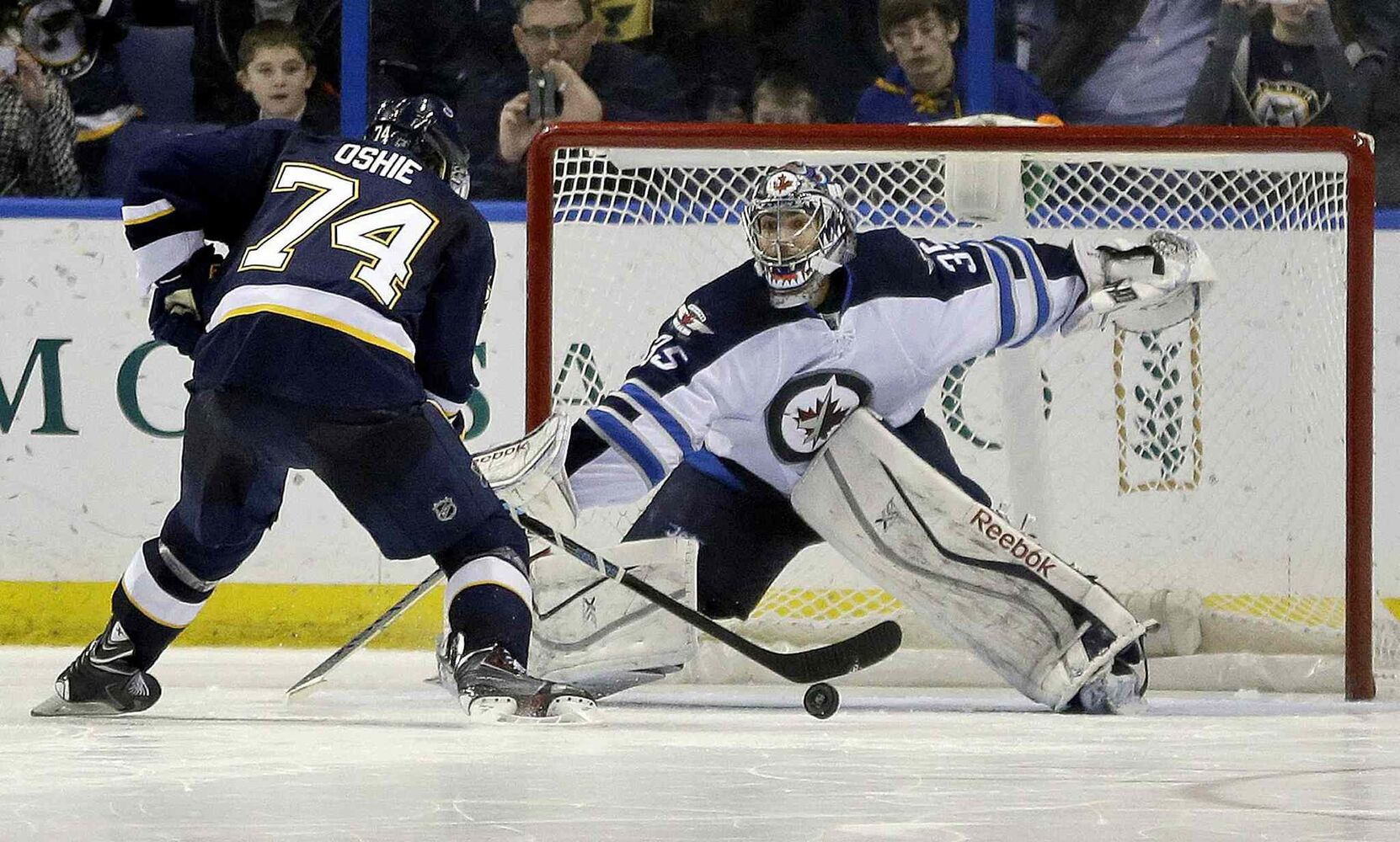 St. Louis Blues' T.J. Oshie, left, scores against Winnipeg Jets' goalie Al Montoya. The Blues won 4-3 in a shootout. (Jeff Roberson / The Associated Press)