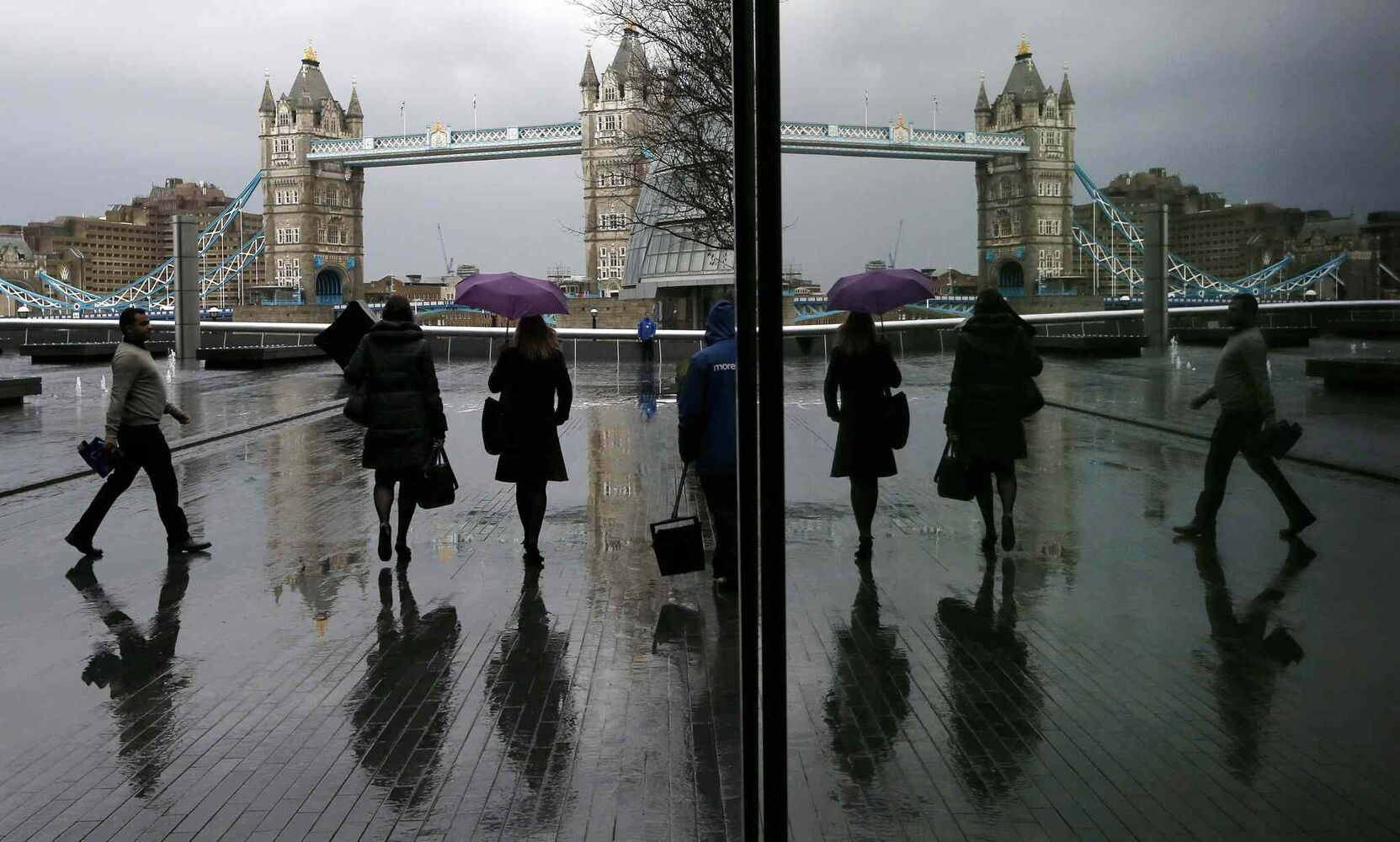 Pedestrians are reflected in a window as they walk through rain near Tower Bridge in London, Tuesday. At least three people have died in a wave of stormy weather that has battered Britain since last week, including a man killed when his mobility scooter fell into a river in Oxford, southern England.  (Kirsty Wigglesworth / The Associated Press)