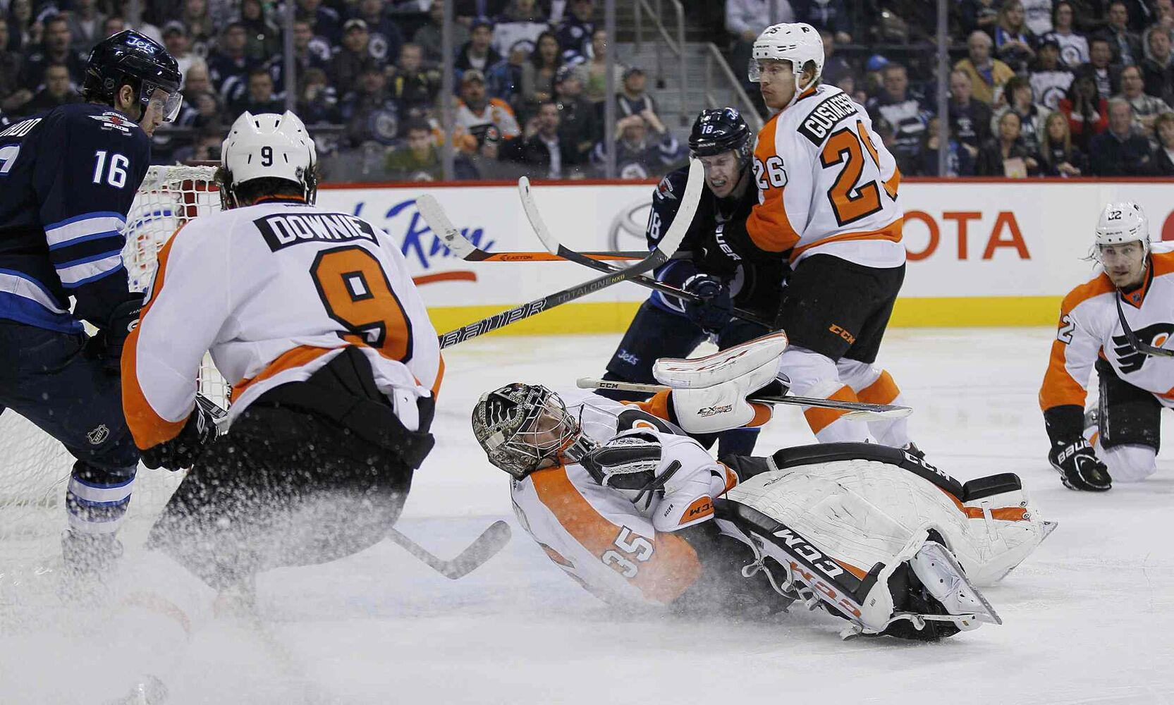Philadelphia Flyers goaltender Steve Mason (35) stops the shot from Winnipeg Jets captain Andrew Ladd (16) as Erik Gustafsson (26) of the Flyers holds back Jets centre Bryan Little (18) as he looks for the rebound during the second period. (JOHN WOODS / THE CANADIAN PRESS)
