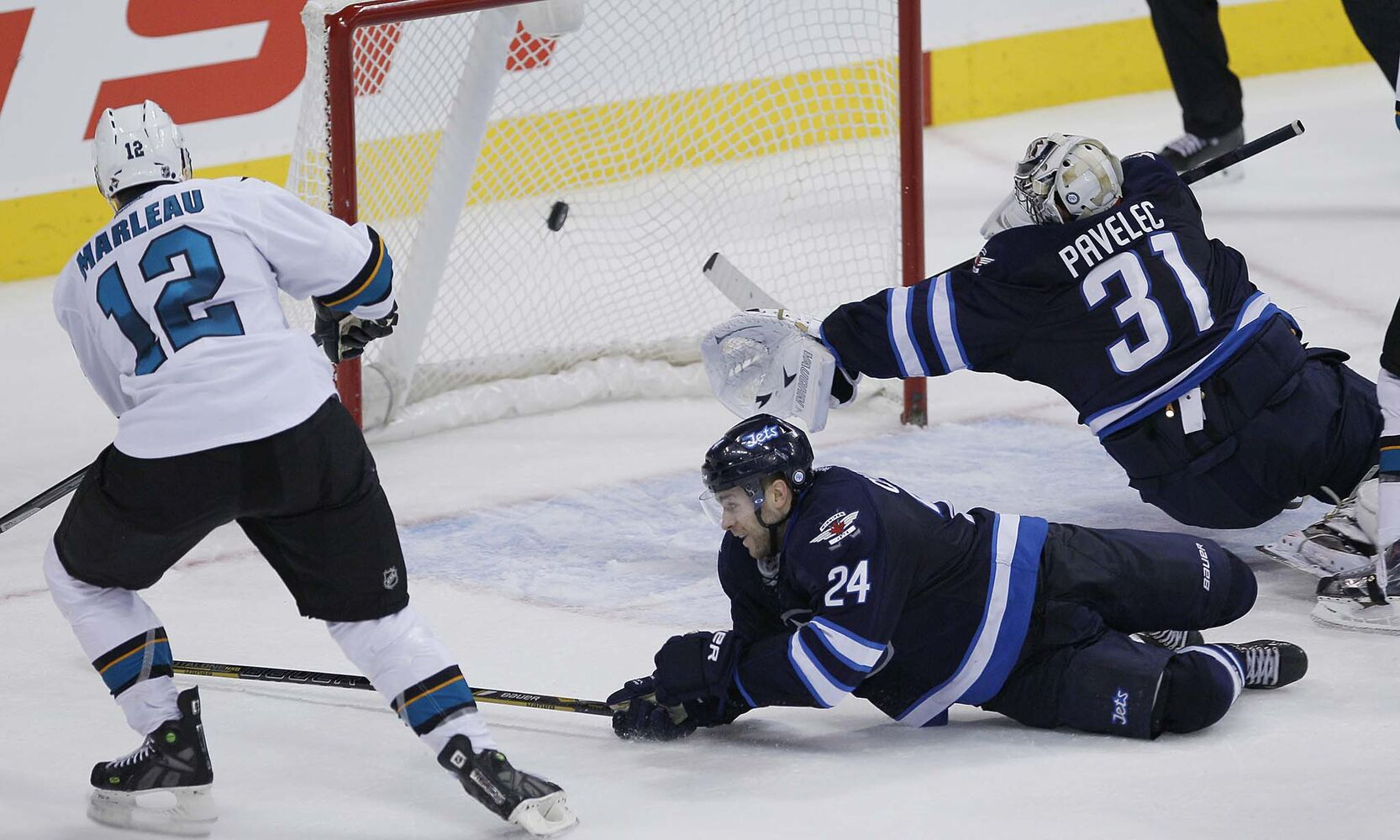 San Jose Sharks' Patrick Marleau (12) scores on Winnipeg Jets' goaltender Ondrej Pavelec (31) and Grant Clitsome (24) in NHL overtime action.