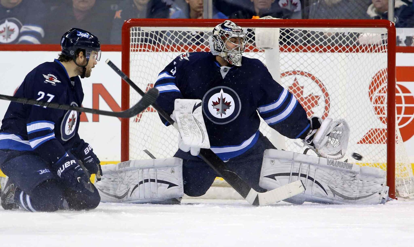Tampa Bay Lightning's Ondrej Palat (18), not shown, scores on Winnipeg Jets goaltender Ondrej Pavelec (31) with Eric Tangradi (27) in the crease during second period.