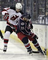 New Jersey Devils' Dainus Zubrus, left, of Lithuania, and Columbus Blue Jackets' James Wisniewski fight for a loose puck during the first period of an NHL hockey game Saturday, Feb. 28, 2015, in Columbus, Ohio. (AP Photo/Jay LaPrete)