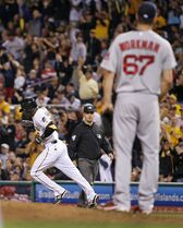 Pittsburgh Pirates' Starling Marte, left, rounds first after hitting a solo home run off Boston Red Sox starting pitcher Brandon Workman (67) during the fifth inning of a baseball game in Pittsburgh Thursday, Sept. 18, 2014. (AP Photo/Gene J. Puskar)