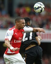 Arsenal's Kieran Gibbs, left, goes to head the ball under pressure from Hull City's Ahmed Elmohamady during the English Premier League soccer match between Arsenal and Hull City at the Emirates stadium in London Saturday Oct. 18, 2014. (AP Photo/Alastair Grant)