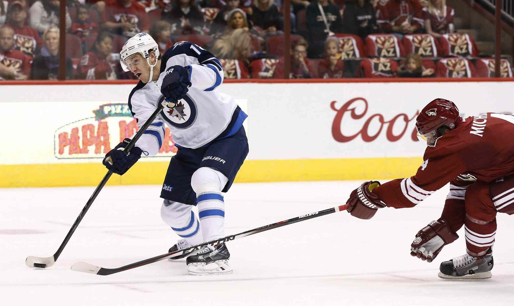 Winnipeg Jets' Bryan Little (18) shoots the puck as he scores a goal while Arizona Coyotes' Zbynek Michalek (4), of the Czech Republic, arrives late to defend during the first period of an NHL hockey game Thursday, Oct. 9, 2014. (Ross D. Franklin / The Associated Press)