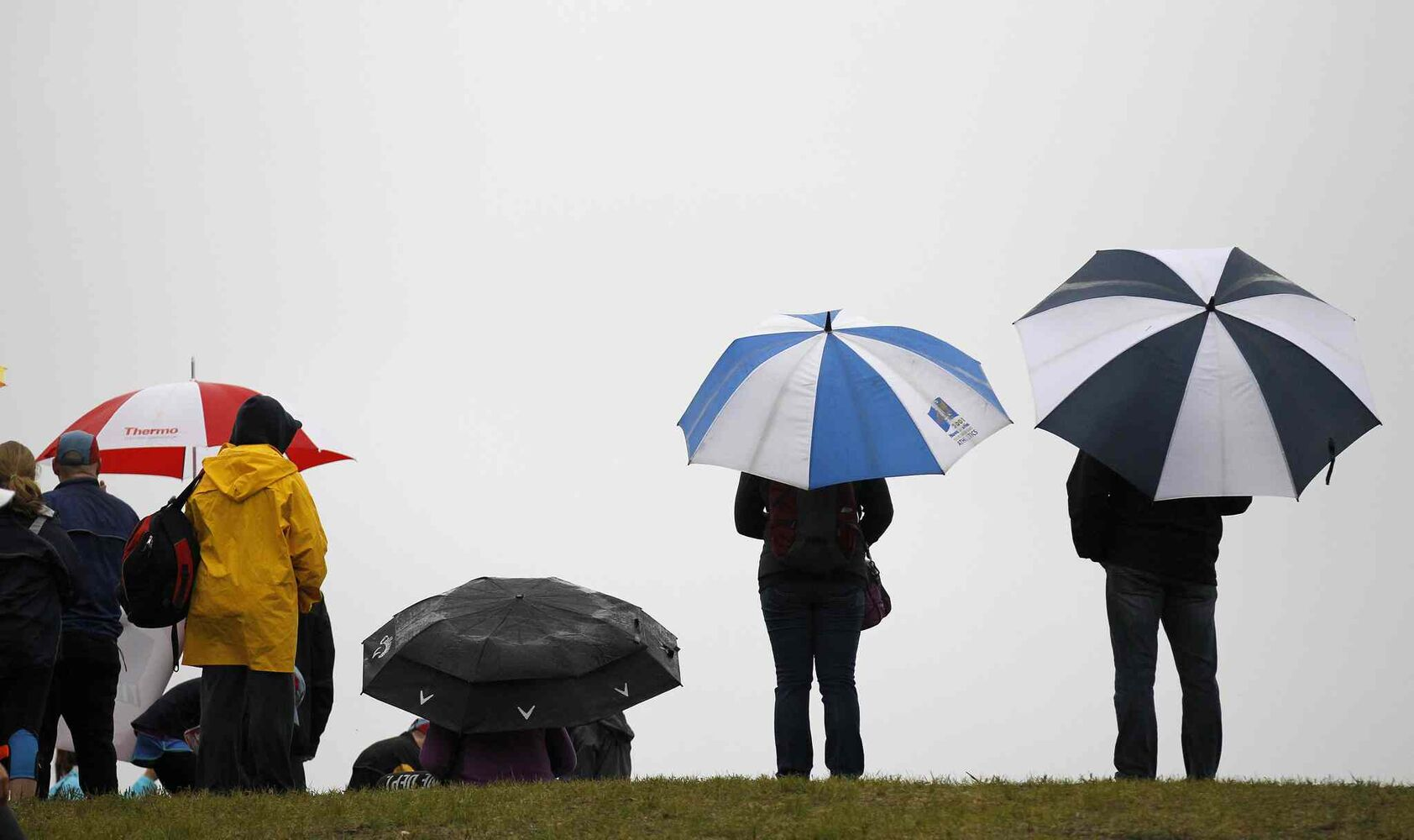 Spectators and supporters with umbrella's during the Manitoba Marathon at the University of Manitoba Sunday. (Trevor Hagan / Winnipeg Free Press)