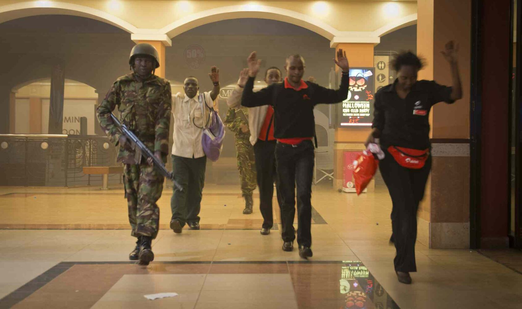 Civilians who had been hiding during the gun battle hold their hands in the air as a precautionary measure before being searched by armed police leading them to safety, inside the Westgate Mall in Nairobi, Kenya, Saturday. Gunmen threw grenades and opened fire Saturday, killing at least 22 people in an attack targeting non-Muslims at an upscale mall in Kenya's capital that was hosting a children's day event, a Red Cross official and witnesses said.  (Jonathan Kalan / The Associated Press)