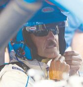 NASCAR Legend Richard Petty straps his helmet on before driving on track to commemorate his 200th win in NASCAR .