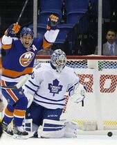 New York Islanders center Frans Nielsen (51), of Denmark, reacts as Toronto Maple Leafs goalie Jonathan Bernier (45) spots the puck in the net after Islanders defenseman Nick Leddy, not seen, scored a goal in the first period of an NHL hockey game in Uniondale, N.Y., Tuesday, Oct. 21, 2014. (AP Photo/Kathy Willens)
