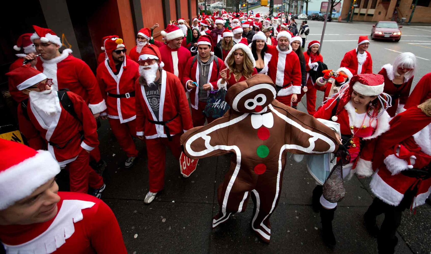 A man dressed as a gingerbread man wanders among hundreds of people dressed as Santa Claus to a pub on Main St. in Vancouver. (DARRYL DYCK / THE CANADIAN PRESS)
