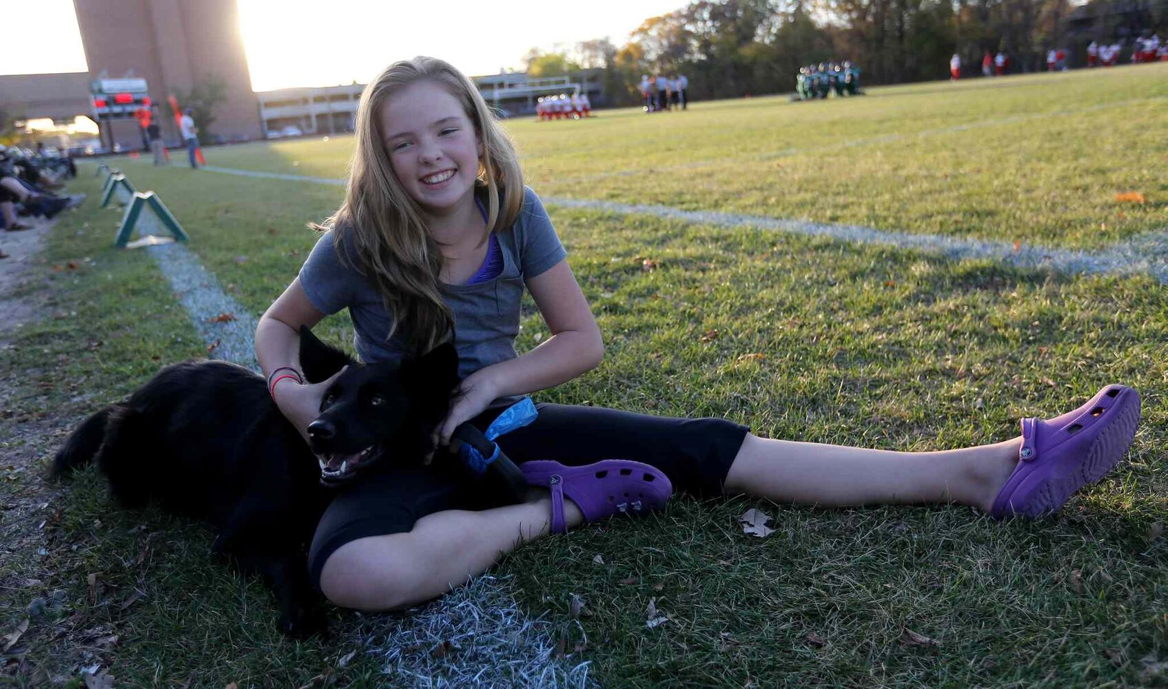 Hannah Hudson, 12, and her dog Molly watch the game from the sideline. (TREVOR HAGAN / WINNIPEG FREE PRESS)