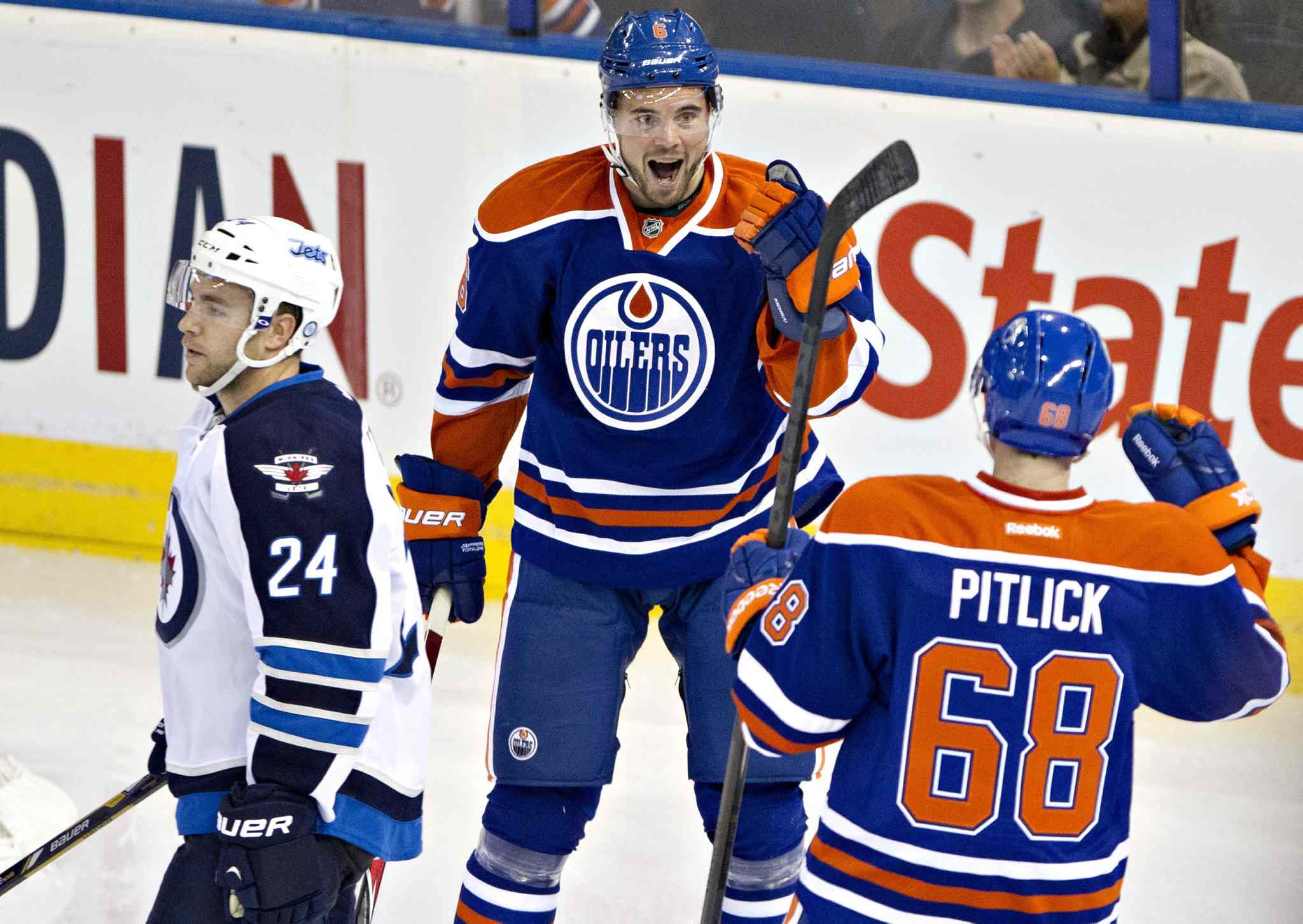 Winnipeg Jets defenceman Grant Clitsome skates by as Edmonton Oilers Jesse Joensuu (6) and Tyler Pitlick (68) celebrate a goal during the second period.