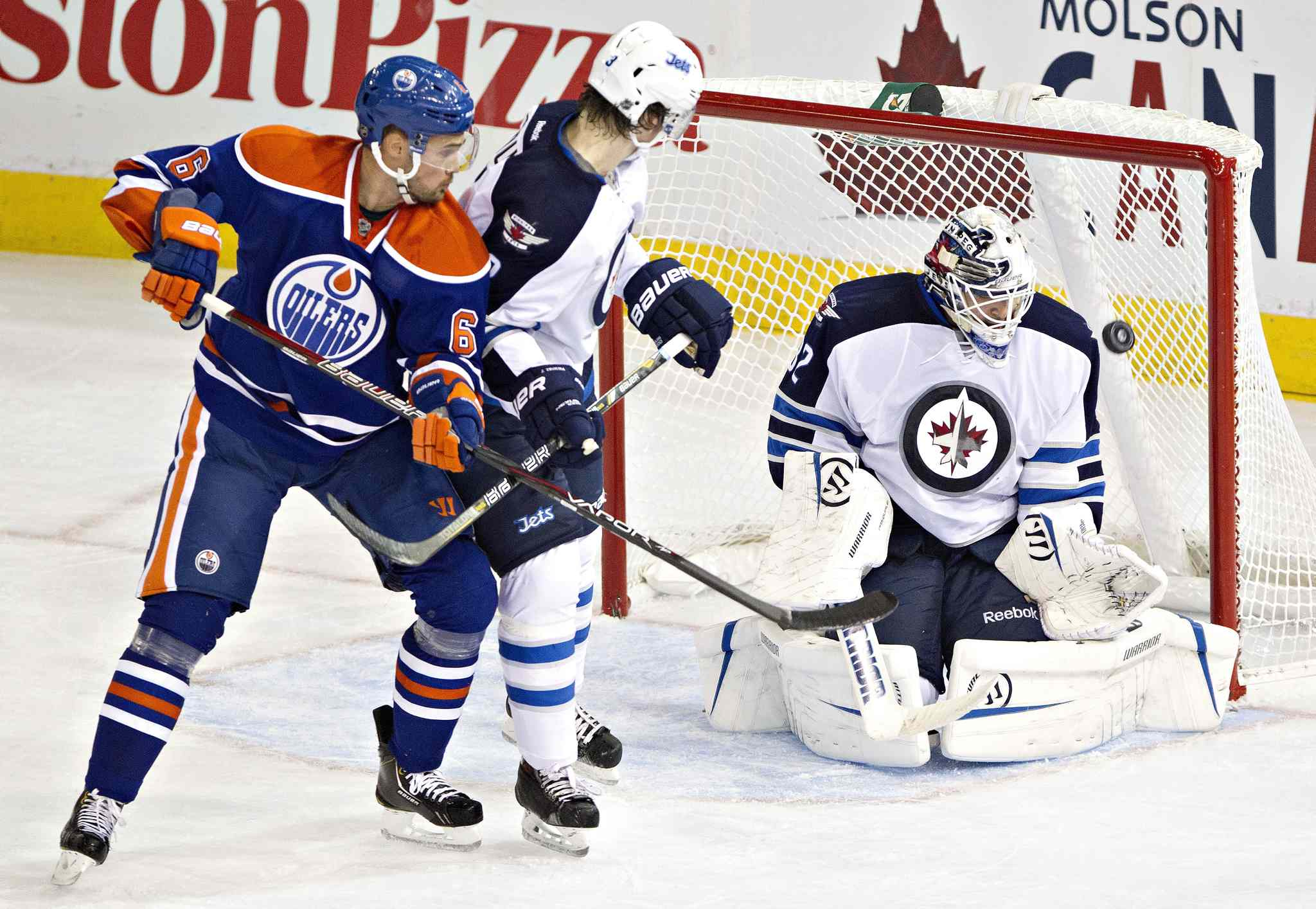 Winnipeg Jets goalie Edward Pasquale (32) makes a save as Jacob Trouba (3) and Edmonton Oilers Jesse Joensuu (6) battle in front during the second period.