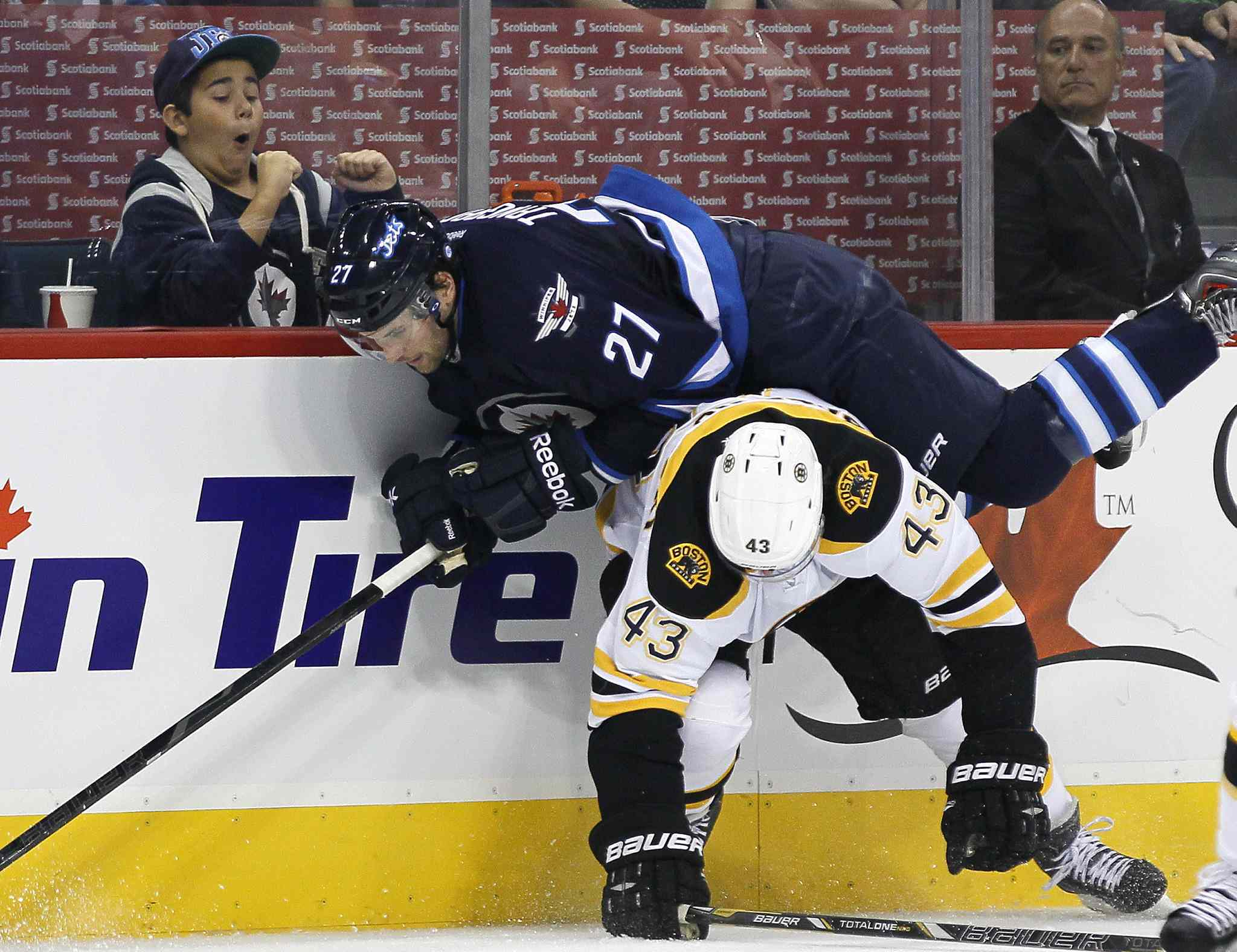 Eric Tangradi is checked by Boston Bruins' Matt Bartkowski.