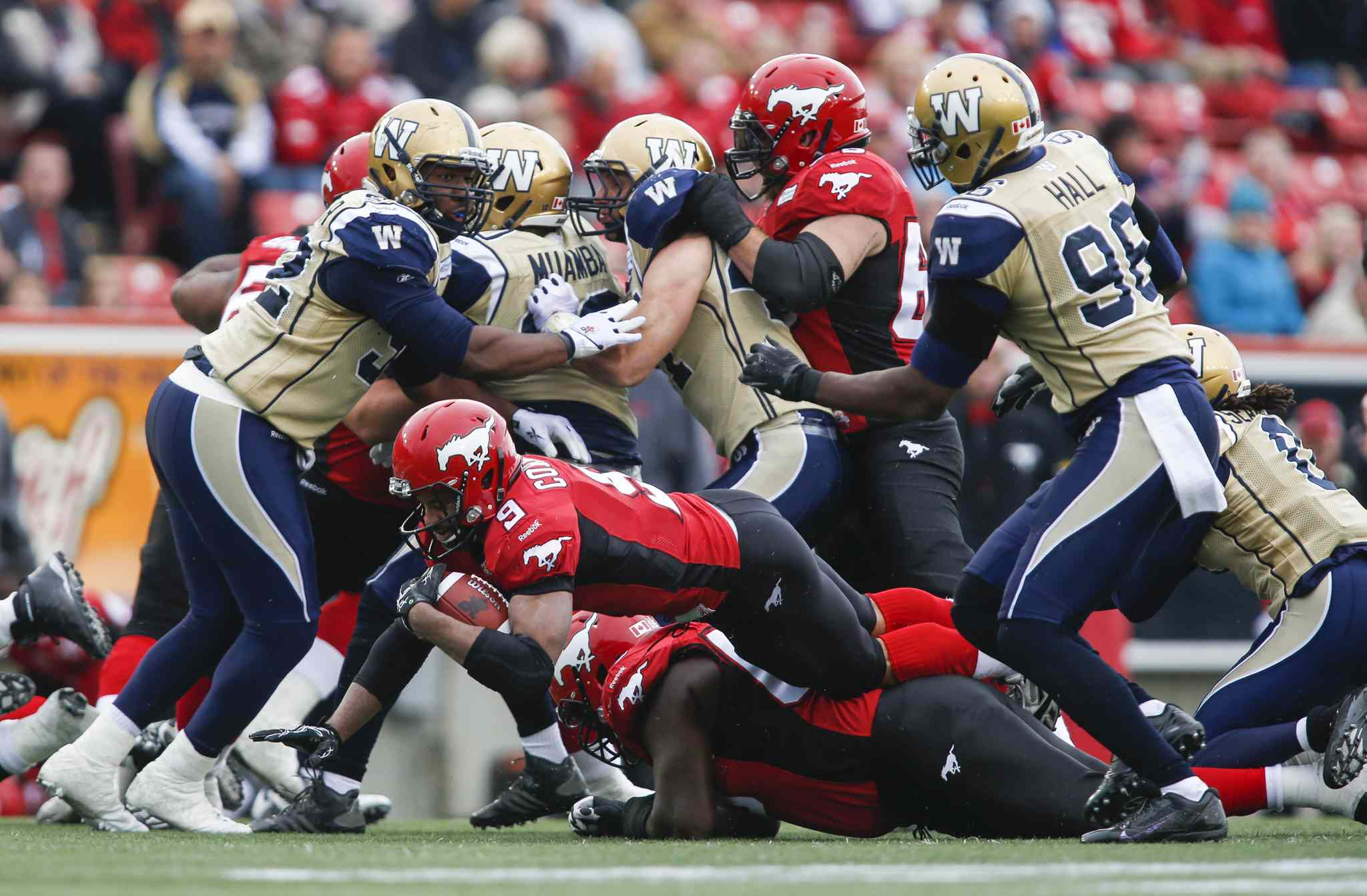Winnipeg Blue Bombers' Bryant Turner Jr. (left) and Alex Hall (right) look on as Calgary Stampeders' Jon Cornish (centre) dives for more yards during the first half.