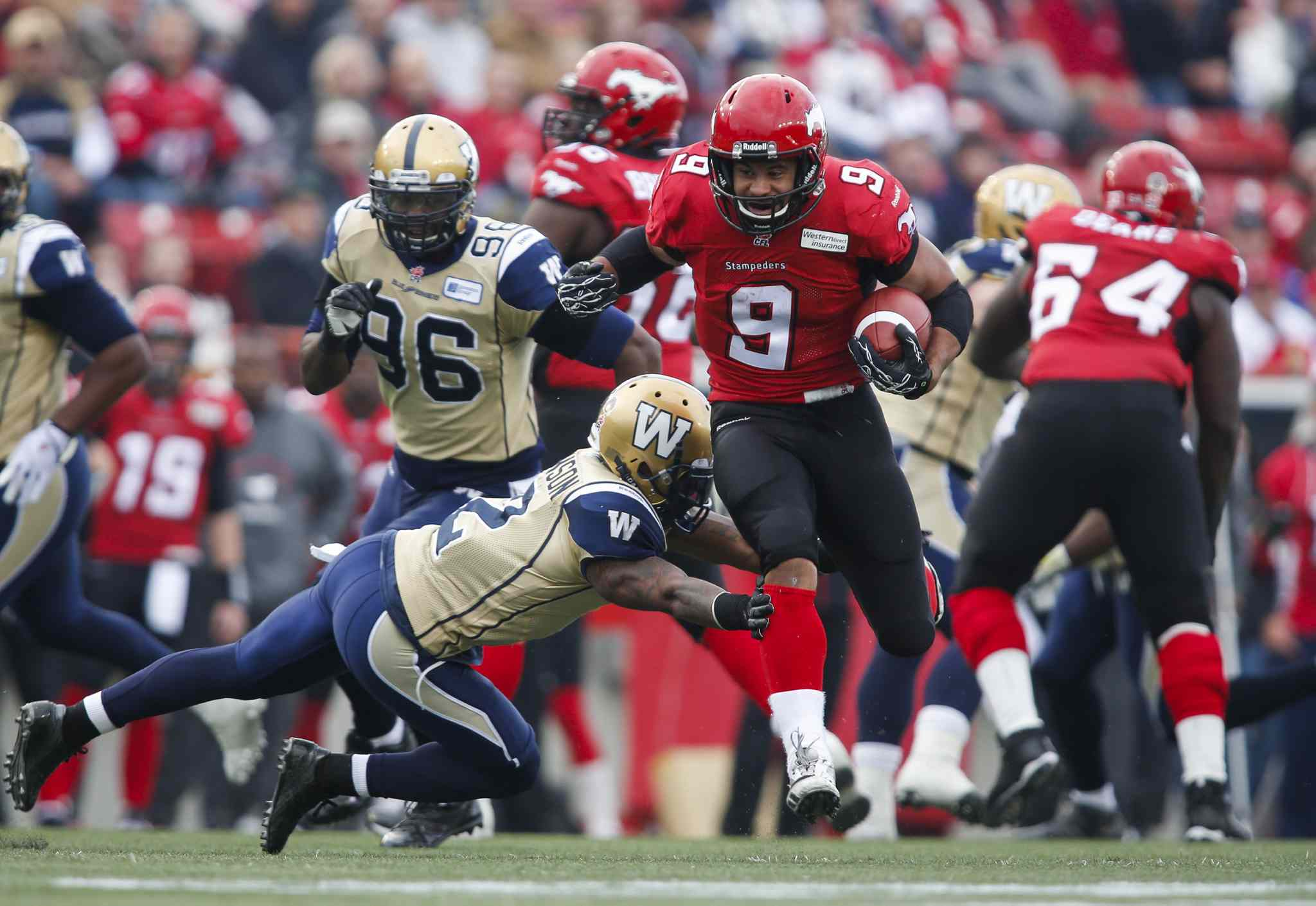 Winnipeg Blue Bombers' Jovon Johnson (bottom) tries to stop Calgary Stampeders' Jon Cornish on his way to a touchdown during the first half.