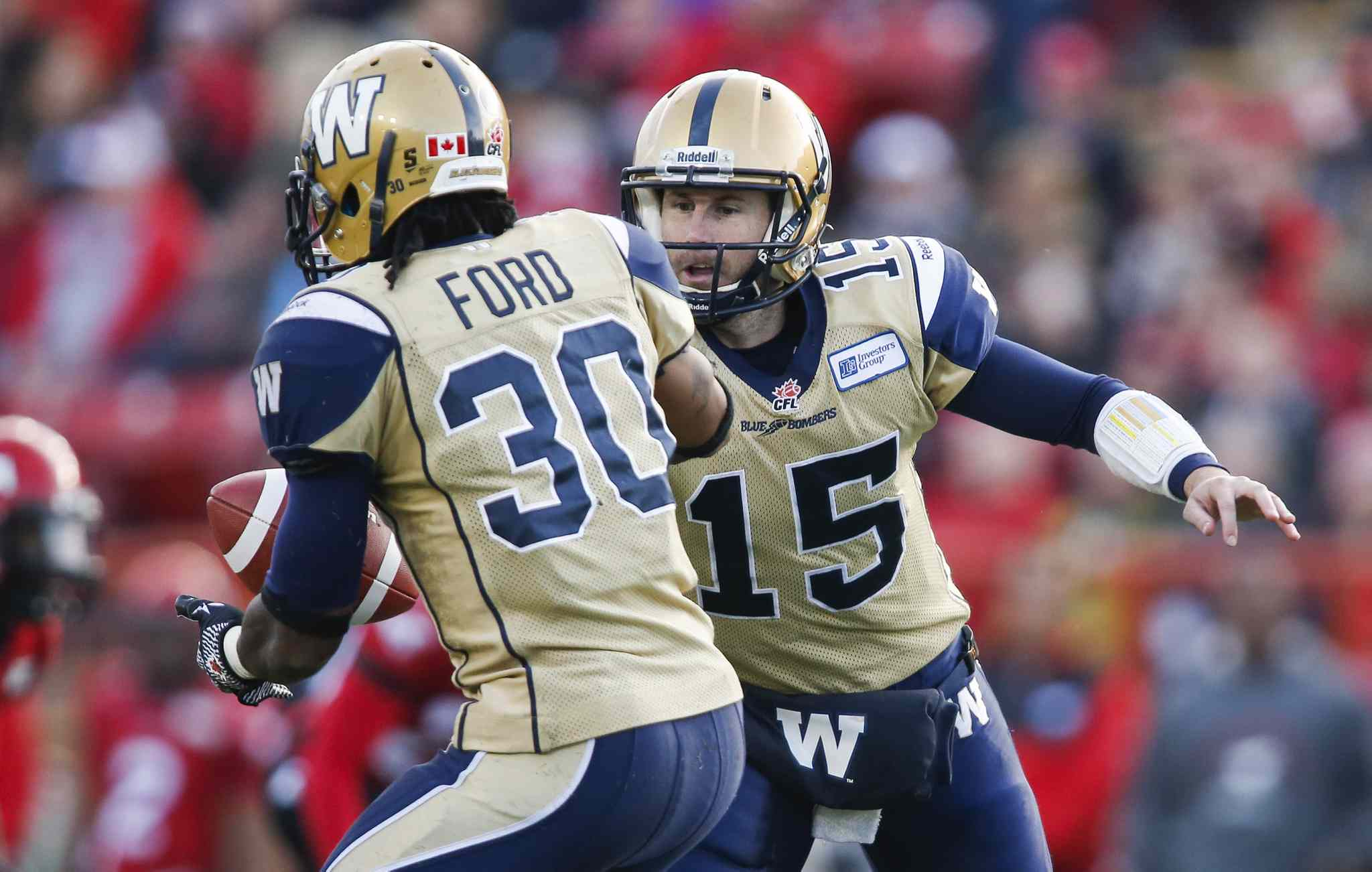 Winnipeg Blue Bombers quarterback Max Hall hands off the ball to teammate Will Ford during the first half.