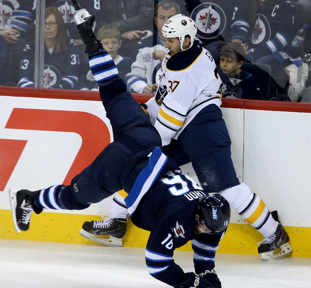 Winnipeg Jets' Andrew Ladd (#16) is tripped up as he collides with Buffalo Sabres' Matt Ellis (#37) during the third period Tuesday.