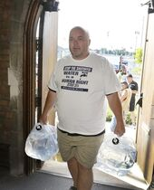 Rob McGuffin, of Windsor, Ontario, carries water jugs into St. Peter's Episcopal Church in Detroit, Thursday, July 24, 2014, for a water station being set up to help Detroit residents who need water. A small group of Canadians brought 1,000 liters (264 gallons) of water from Windsor, Ontario, to Detroit to protest thousands of residential service shutoffs by Detroit's water department. (AP Photo)