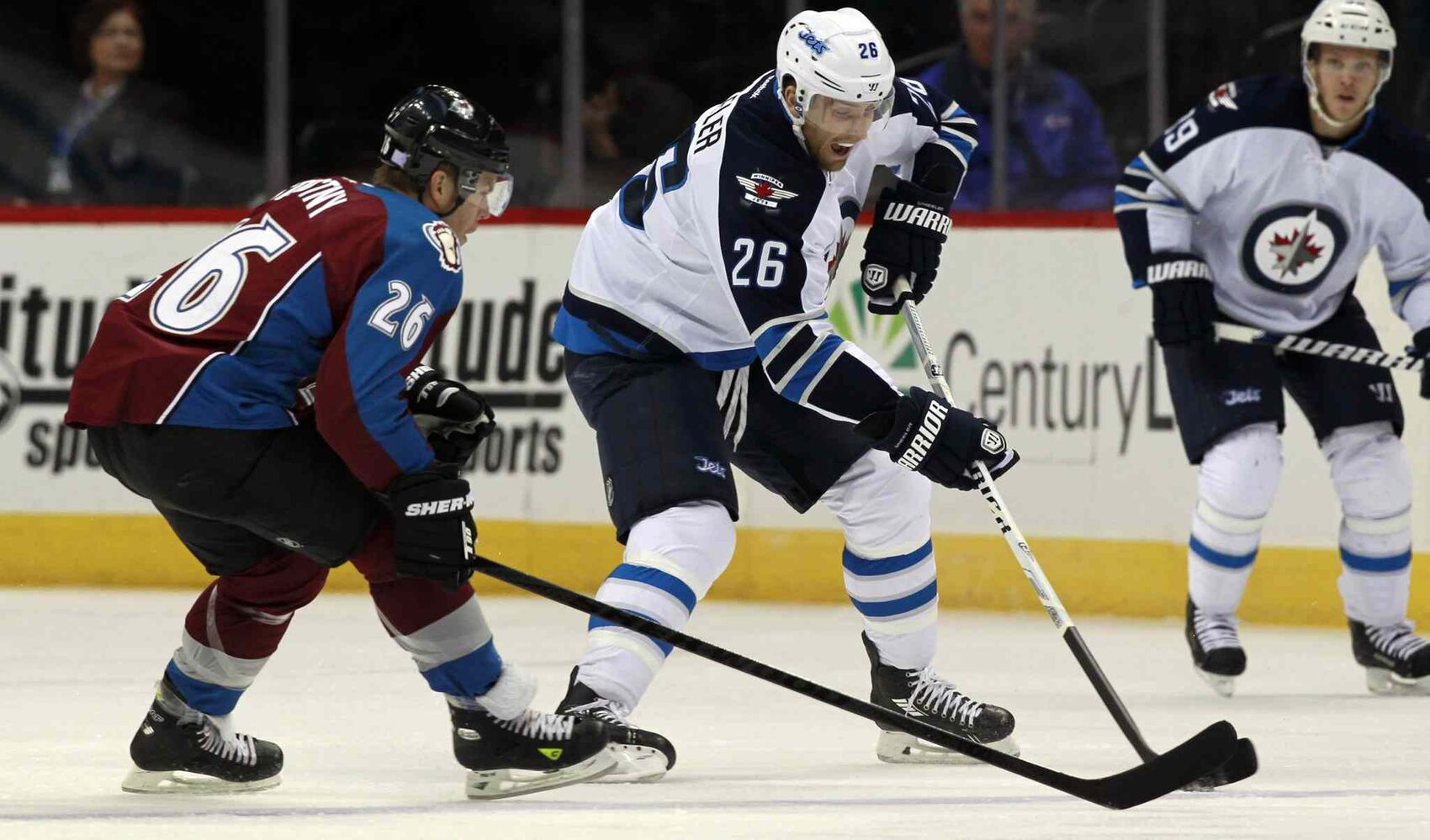 Winnipeg Jets winger Blake Wheeler (centre) picks up the loose puck as Colorado Avalanche center Paul Stastny (left) gives chase during the first period Sunday's game in Denver, Colo. (David Zalubowski / The Associated Press)