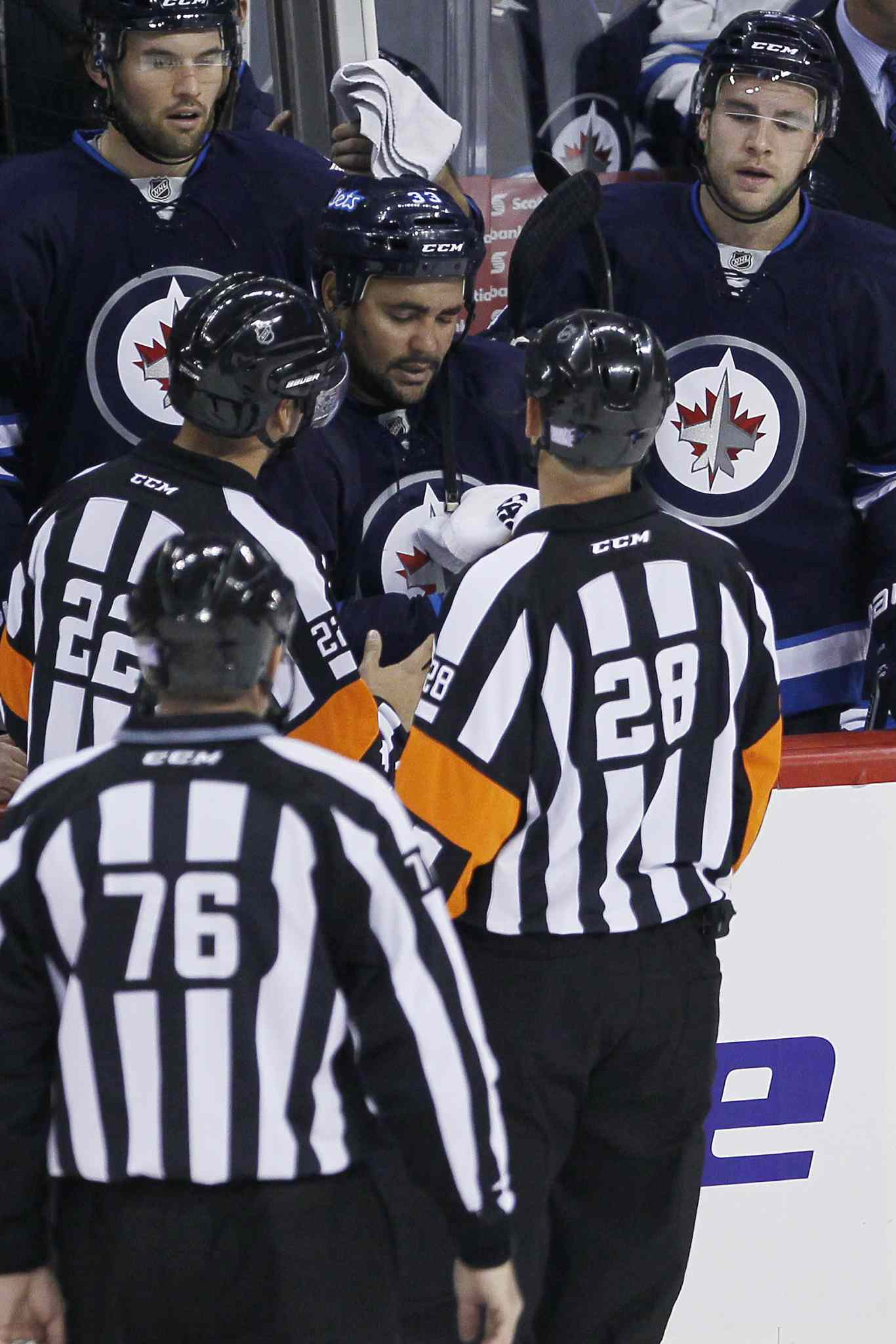 Referees check the eye injury of Winnipeg Jets defenceman Dustin Byfuglien during the first period.