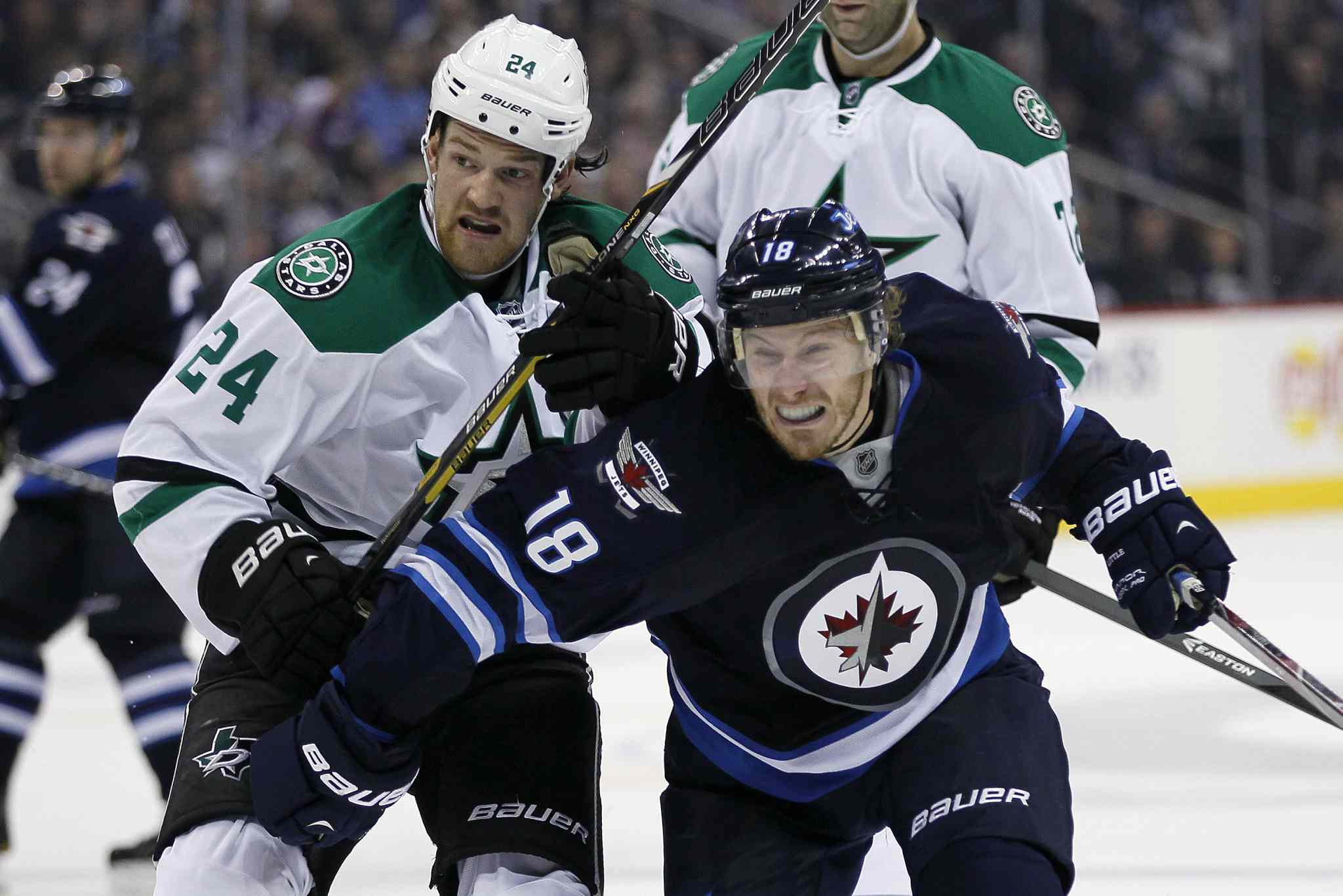 Winnipeg Jets' Bryan Little (18) attempts to get around Dallas Stars' Jordie Benn (24) during the second period.