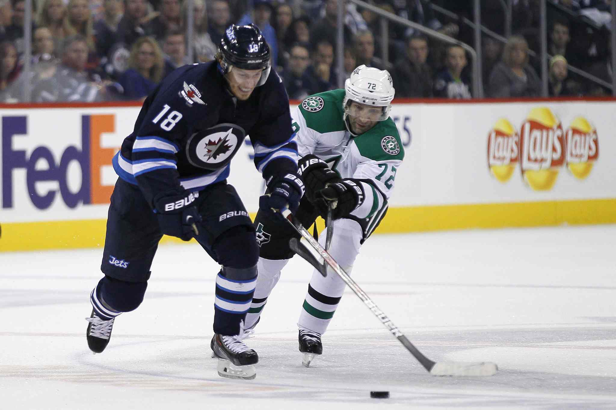 Bryan Little and Dallas Stars forward Erik Cole (72) race for the puck during the second period.