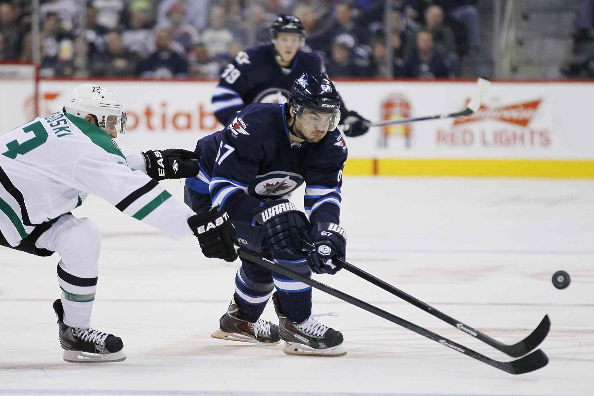 Winnipeg Jets' Michael Frolik (67) and Dallas Stars' Alex Goligoski (33) chase down the puck during the second period.