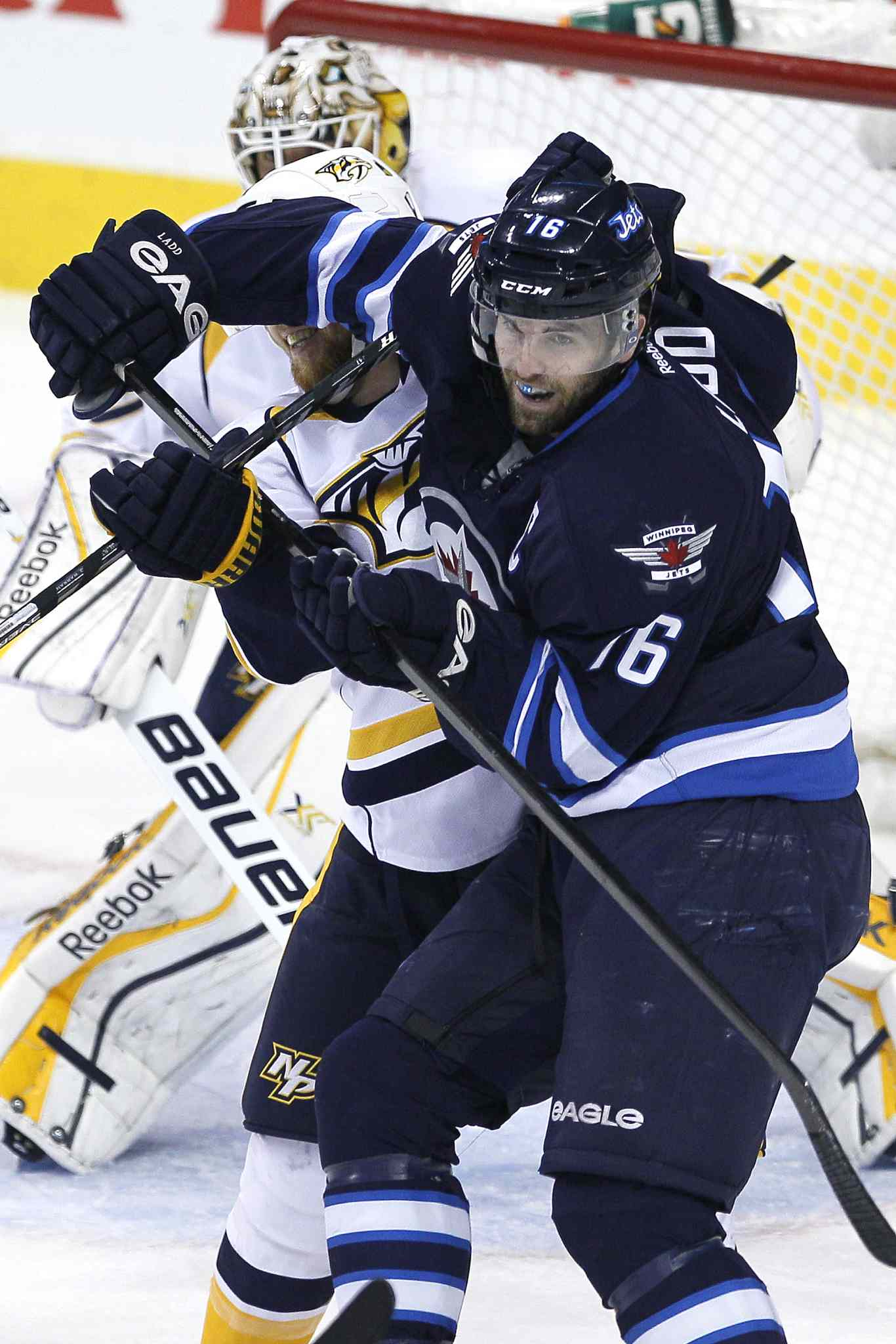 Winnipeg Jets' Andrew Ladd (16) mixes it up with Nashville Predators' Ryan Ellis (4) in front of goaltender Carter Hutton (30) during the first period.
