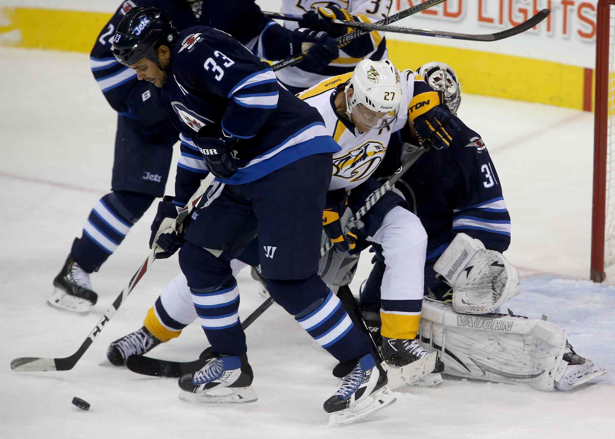 Winnipeg Jets' Dustin Byfuglien blocks a shot as Nashville Predators' Patric Hornqvist (27) screens goaltender Ondrej Pavelec during the first period.