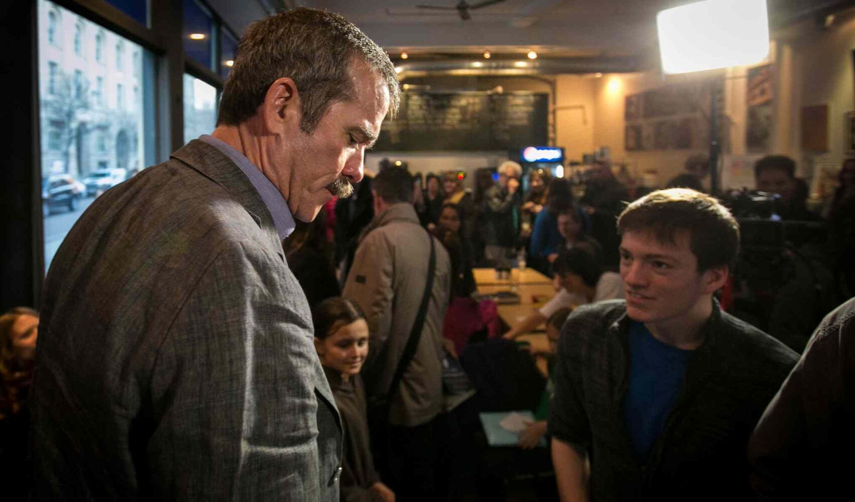 Col. Chris Hadfield leaves through a crowd of fans who packed the Winnipeg Free Press News Café on Wednesday to see the Canadian astronaut in person. (Melissa Tait / Winnipeg Free Press)