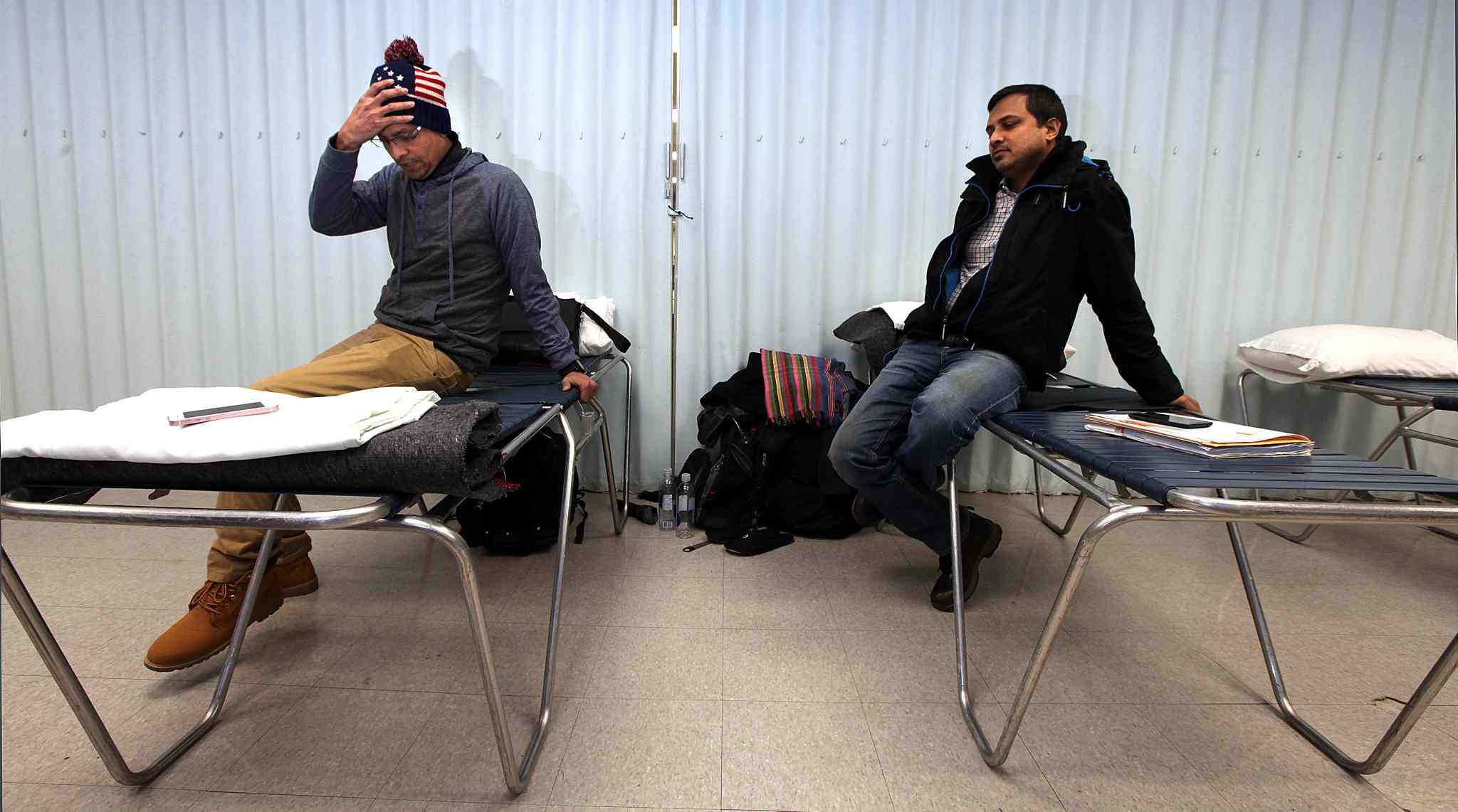 Shahadat  Hossain (left) and  Subir Barman spend time waiting at their Salvation Army overflow sleeping quarters, an area normally part of a dining room.