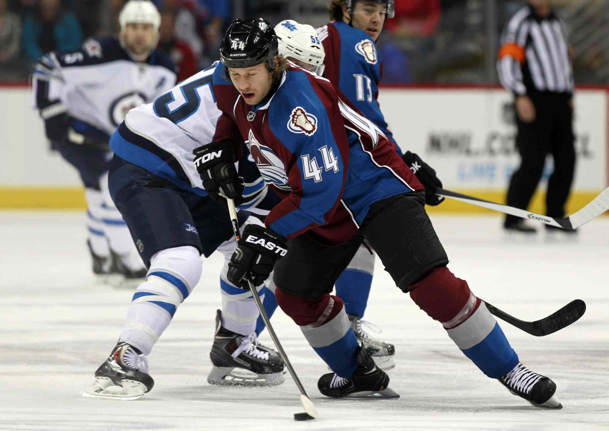 Avalanche defenceman Ryan Wilson (front) picks up the loose puck in the first period.