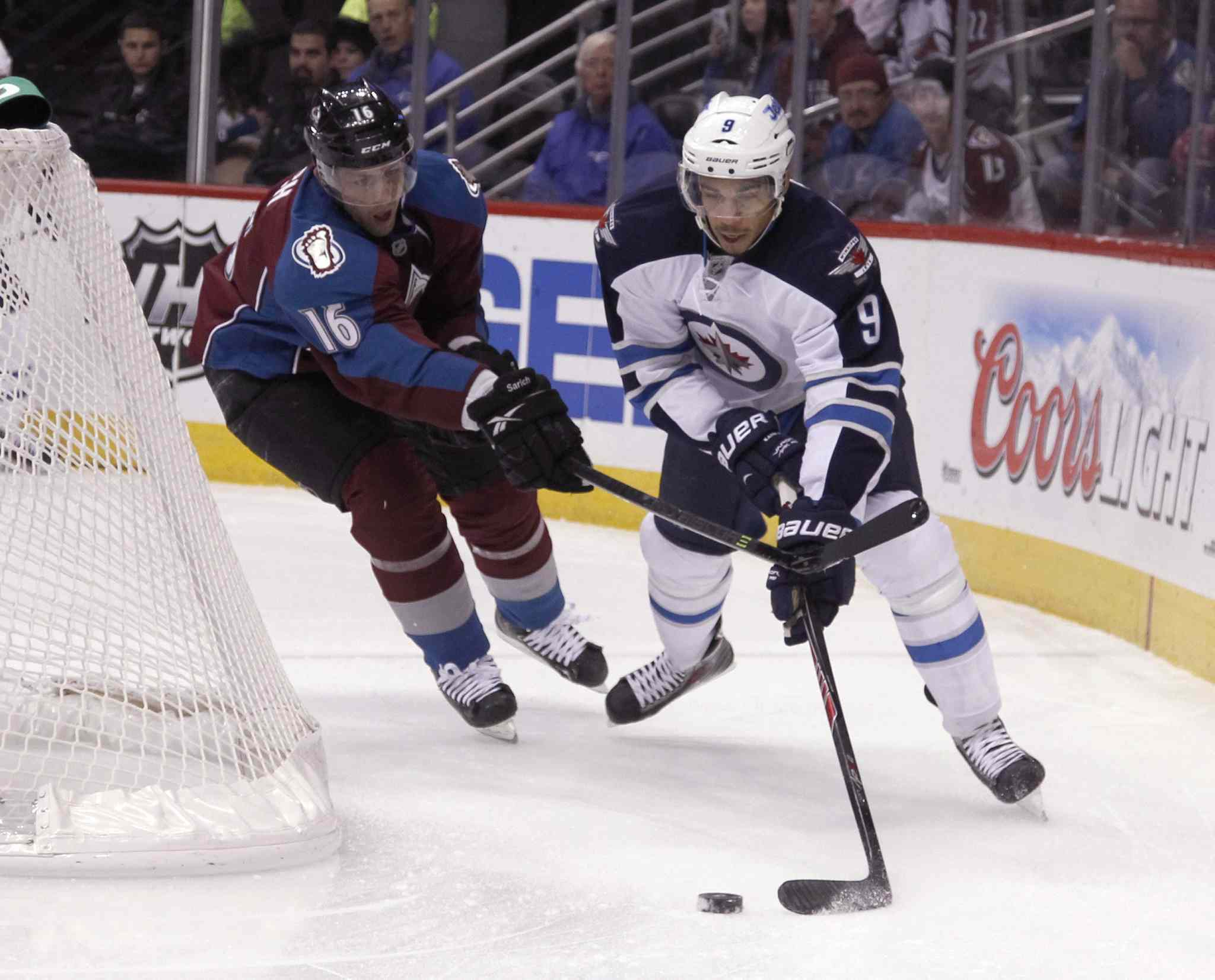 Evander Kane tries a wraparound as Avalanche defenceman Cory Sarich gives chase in the first period.