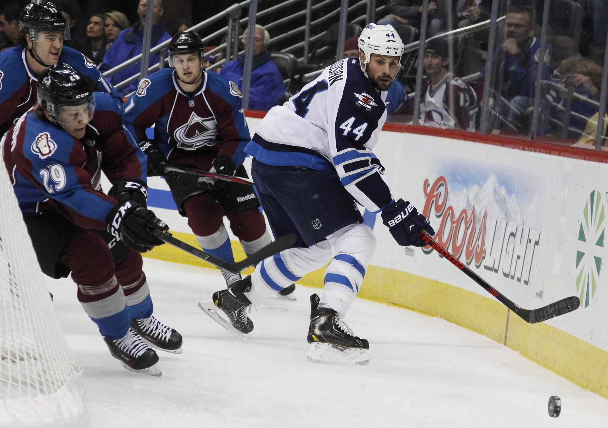 Winnipeg Jets defenseman Zach Bogosian (right) clears the puck from behind the net as Nathan MacKinnon (left) and John Mitchell give chase during the second period.