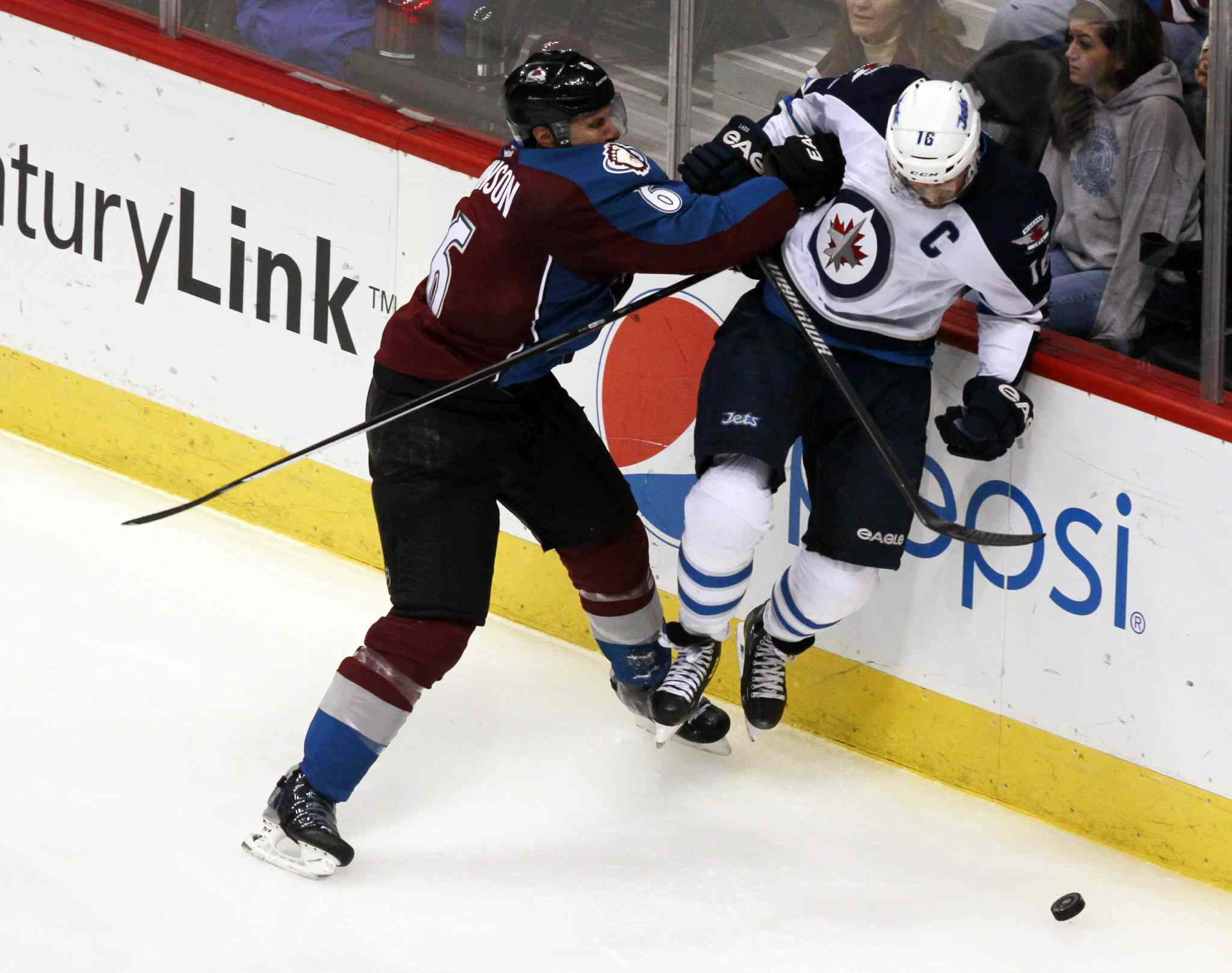 Colorado Avalanche defenseman Erik Johnson (left) sends Jets captain Andrew Ladd into the boards in the third period.