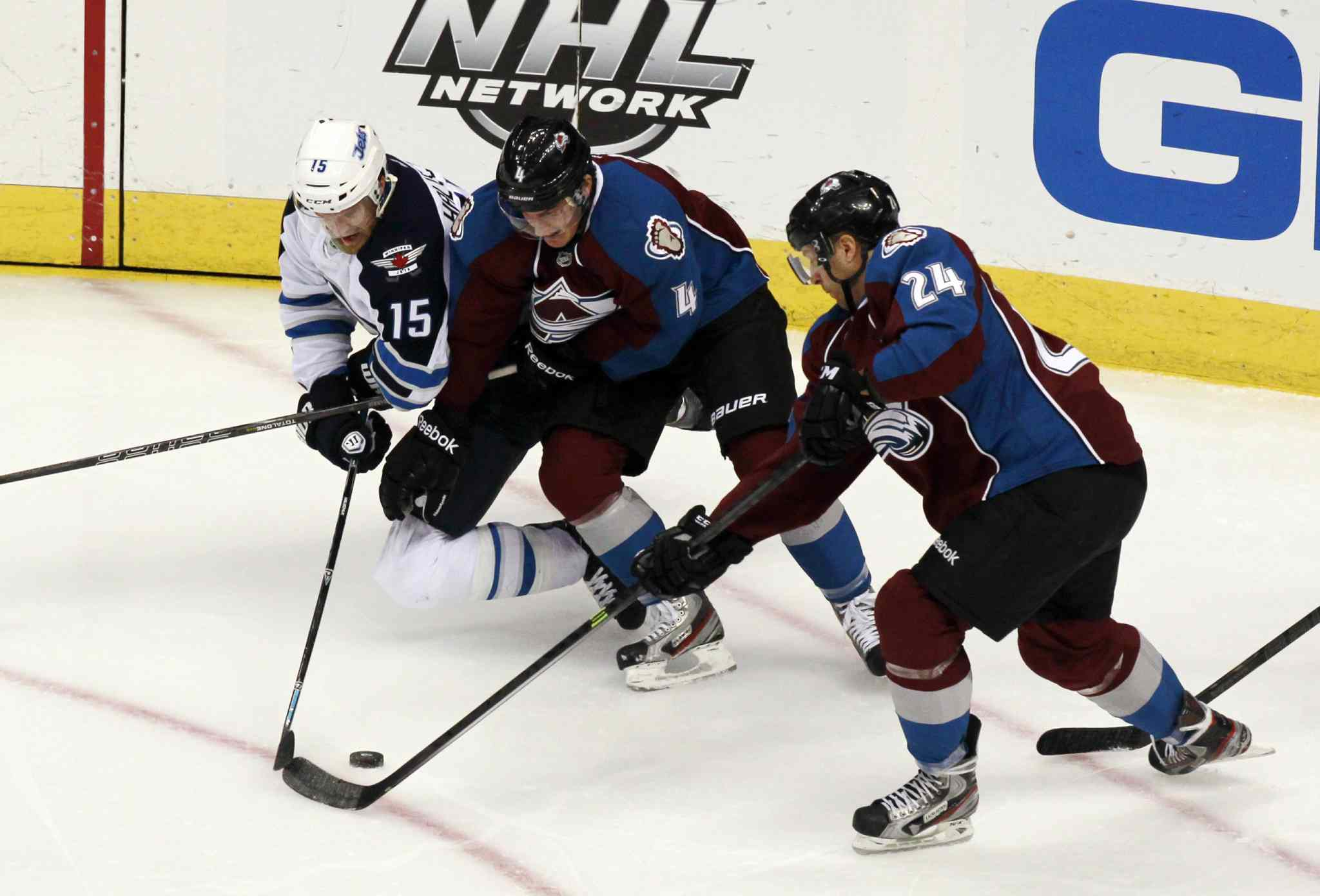 Jets winger Matt Halischuk (left) battles for control of the puck with Colorado Avalanche defenceman Tyson Barrie (centre) and center Marc-Andre Cliche in the third period.
