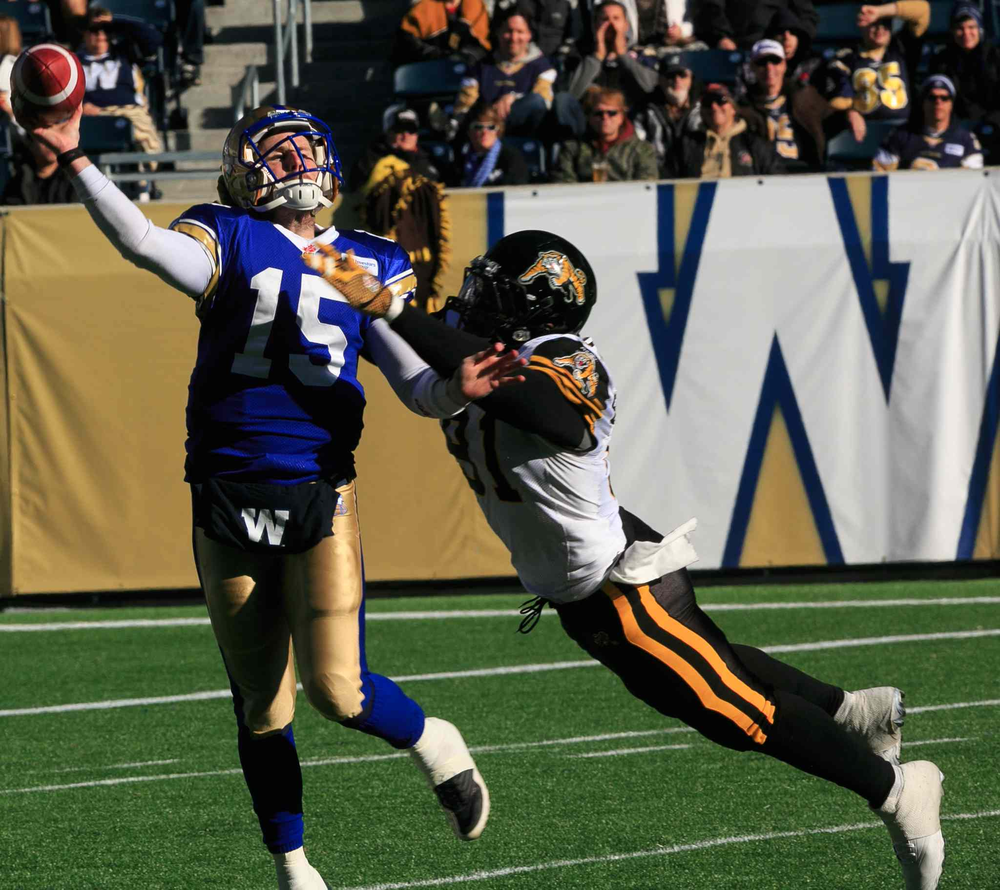 Bombers quarterback Max Hall gets rid of the ball just before he is taken down by Brandon Boudreaux of the Hamilton Tiger-Cats in the first quarter.