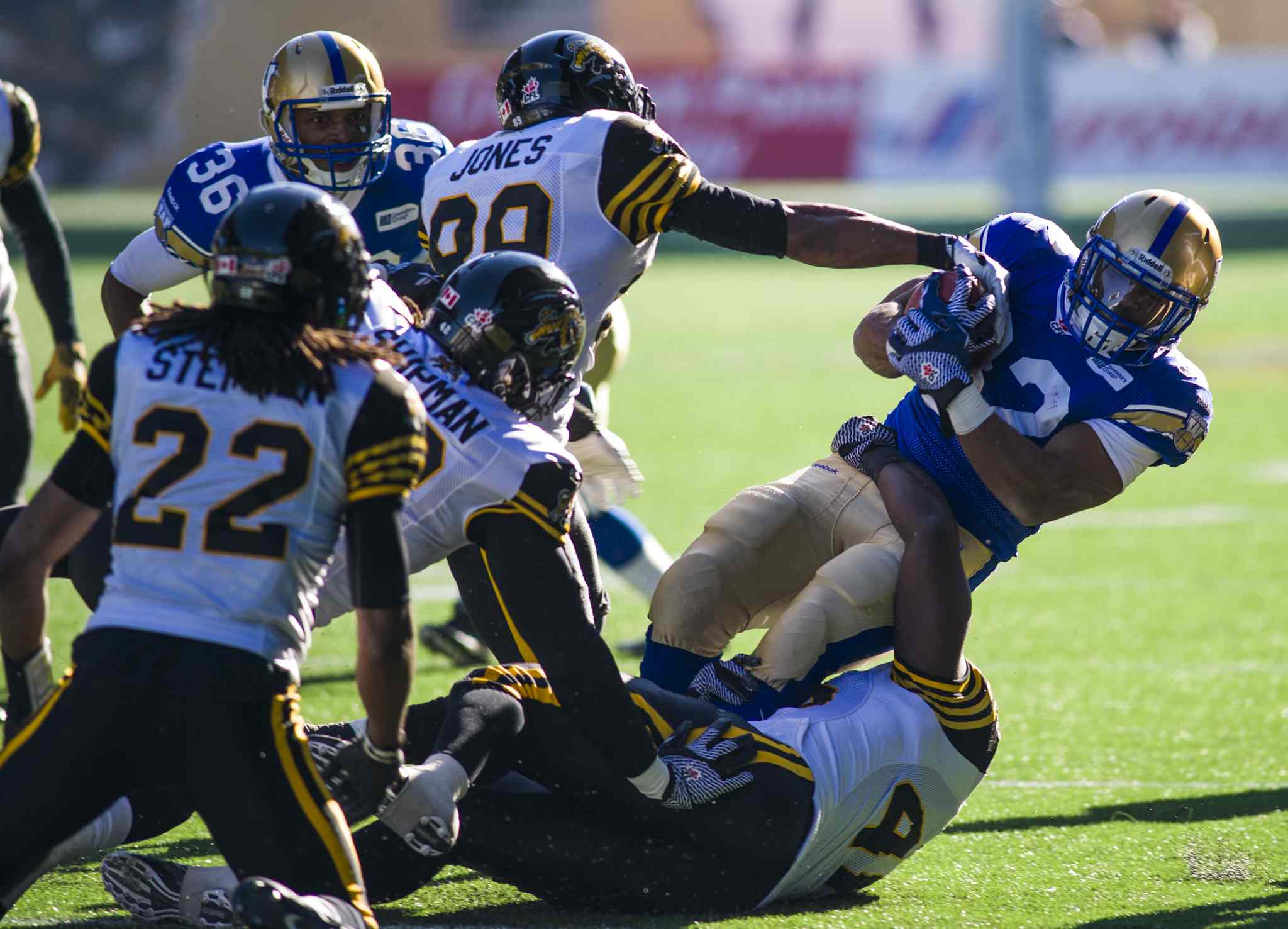 The Winnipeg Blue Bombers Mario Fannin (#32) is taken down by Hamilton Tiger-Cats Onrea Jones (89).