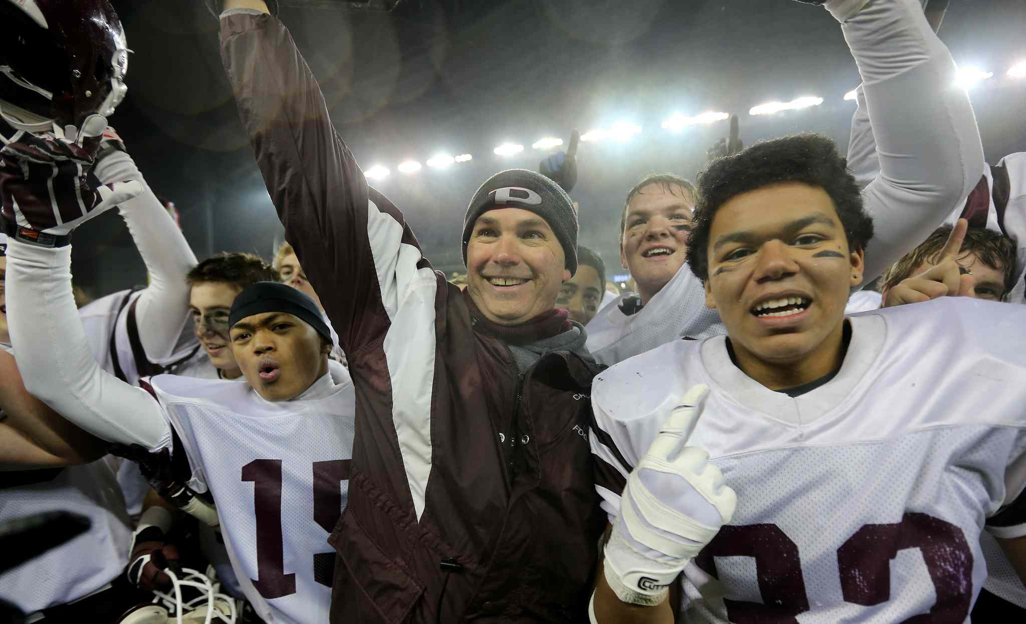 Calvin Diaz (left), head coach Peter Pura (centre) and Trevor Wright of the St.Paul's Crusaders AA football team celebrate their Free Press Bowl Championship victory over the Garden City Fighting Gophers.