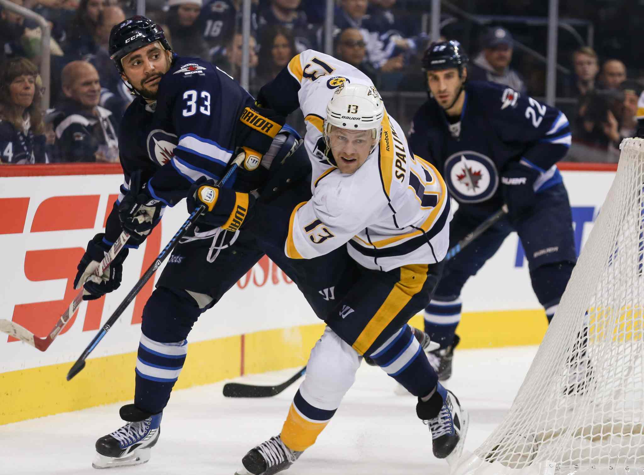 Jets defenceman Dustin Byfuglien holds back Predators' Nick Spaling behind the Jets' net in the first period.