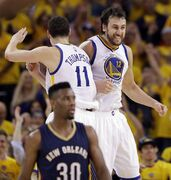 Golden State Warriors' Andrew Bogut (12) celebrates after a dunk with teammate Klay Thompson (11) as New Orleans Pelicans' Norris Cole (30) walks away during the second half in Game 2 of a first-round NBA basketball playoff series Monday, April 20, 2015, in Oakland, Calif. Golden State won 97-87. (AP Photo/Marcio Jose Sanchez)