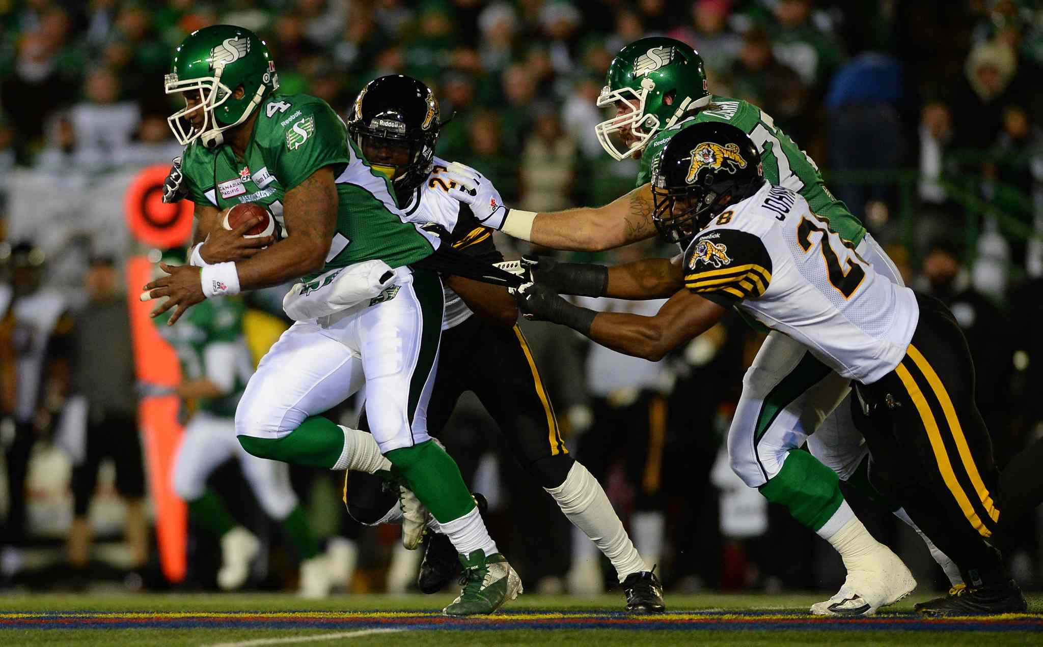 Saskatchewan Roughriders quarterback Darian Durant is grabbed by the jersey by Hamilton Tiger-Cats linebacker Jamall Johnson during the first quarter.