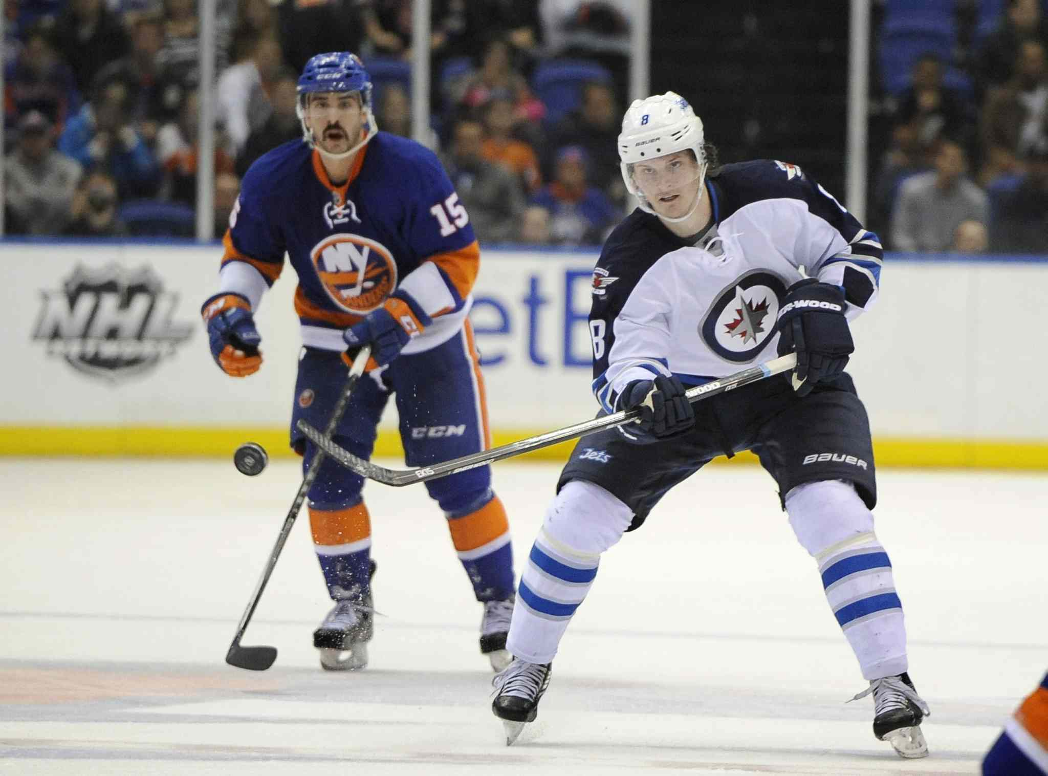 Winnipeg Jets defenceman Jacob Trouba (right) flicks the puck down the ice and away from New York Islanders forward Cal Clutterbuck in the third period.
