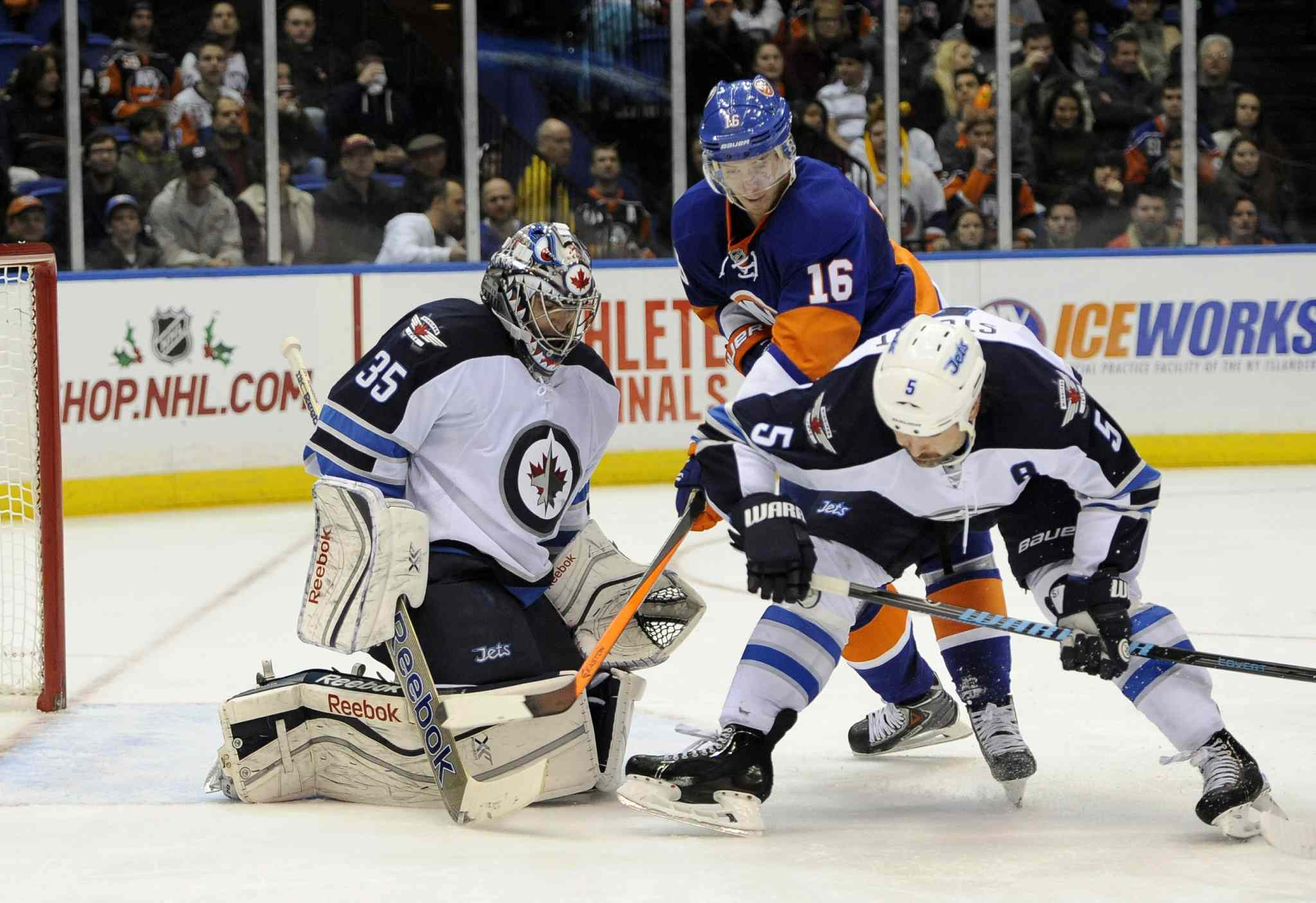 New York Islanders' Peter Regin (centre) and Winnipeg Jets defenceman Mark Stuart (right) scuffle in front of the net as Jets goalie Al Montoya defends during the second period.